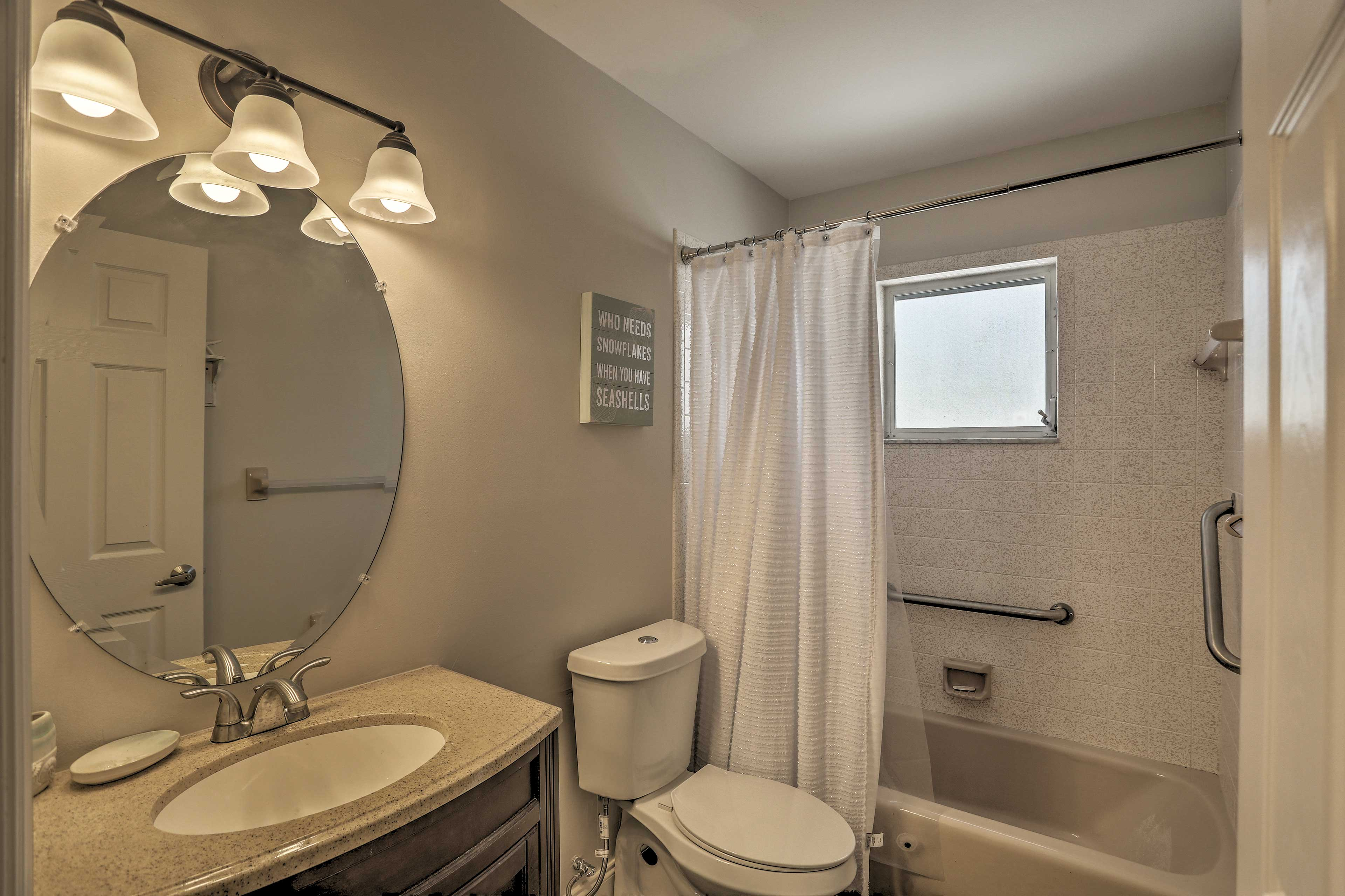 Wash up in this first bathroom, which features grab rails in the shower.