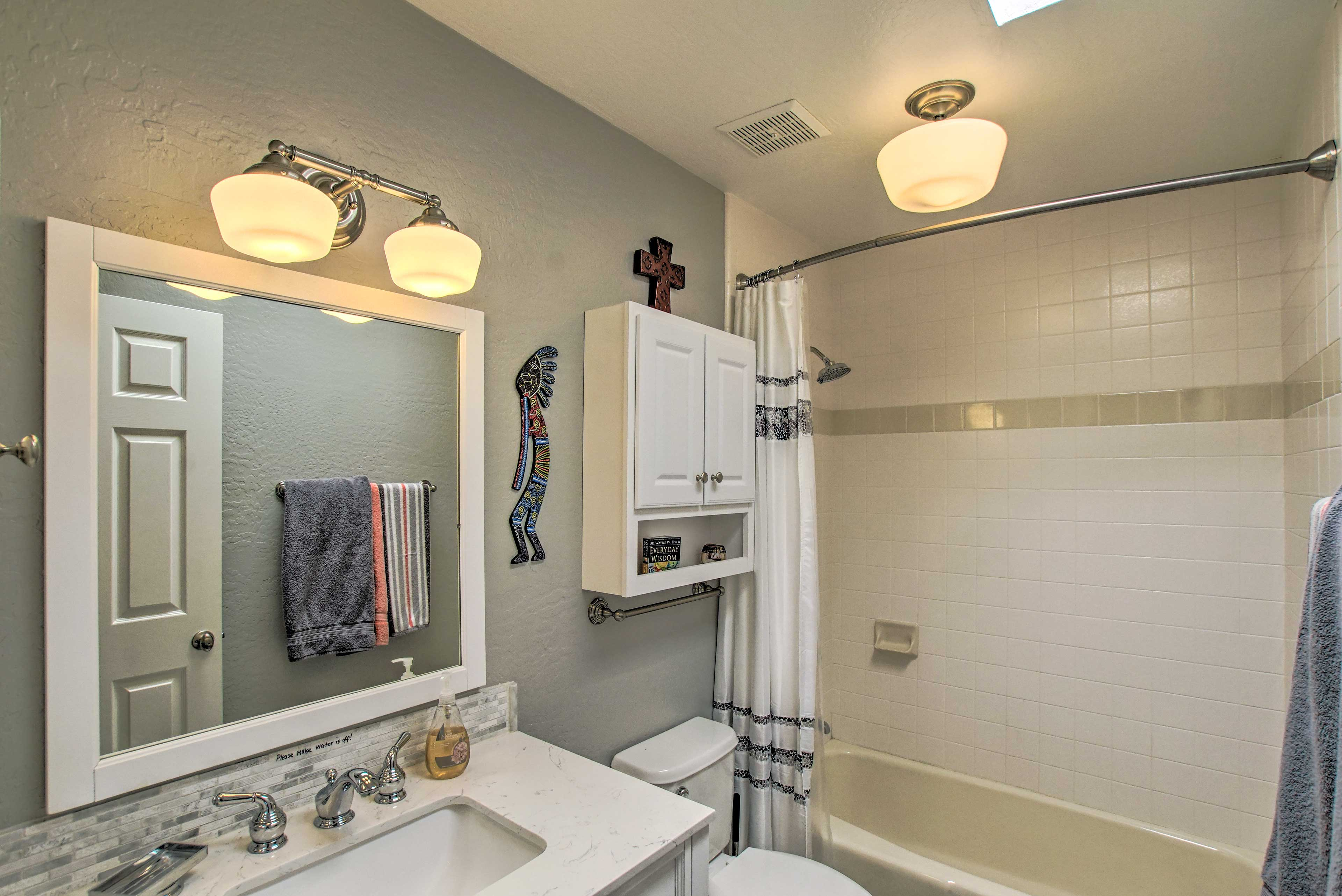 One of 2 full baths, this one hosts a shower/tub combo.