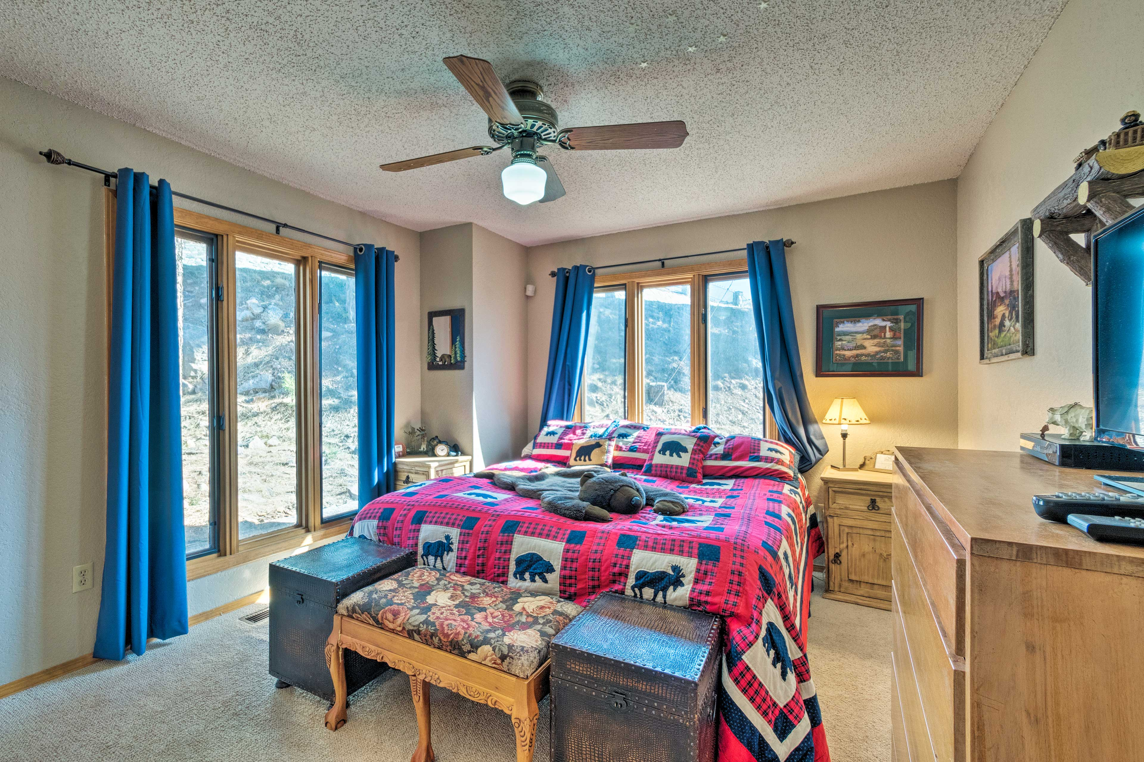 This full bedroom hosts picture windows, a queen bed and a flat-screen TV.