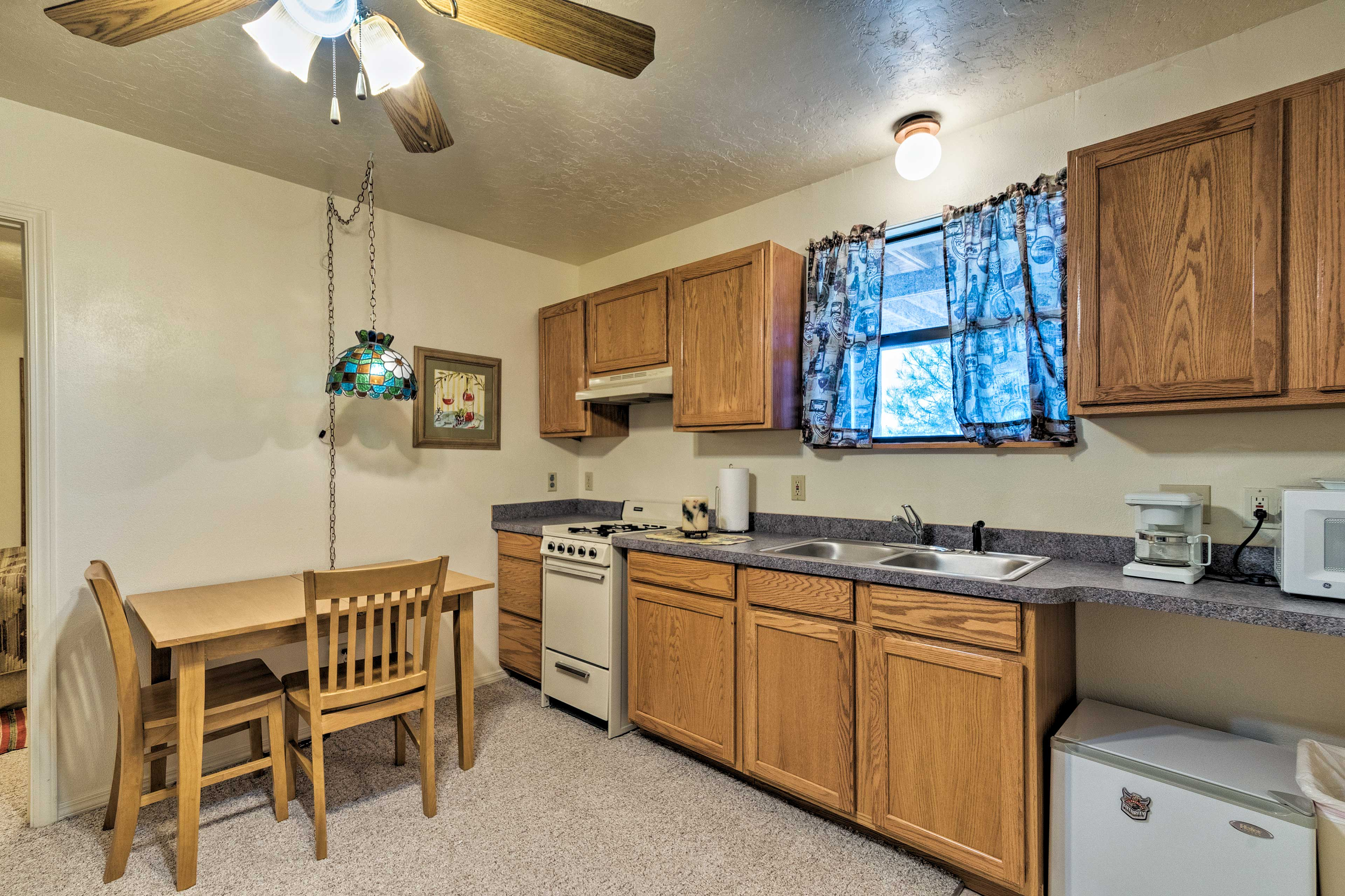 The attached living area hosts a well-equipped kitchen and seating for 2.