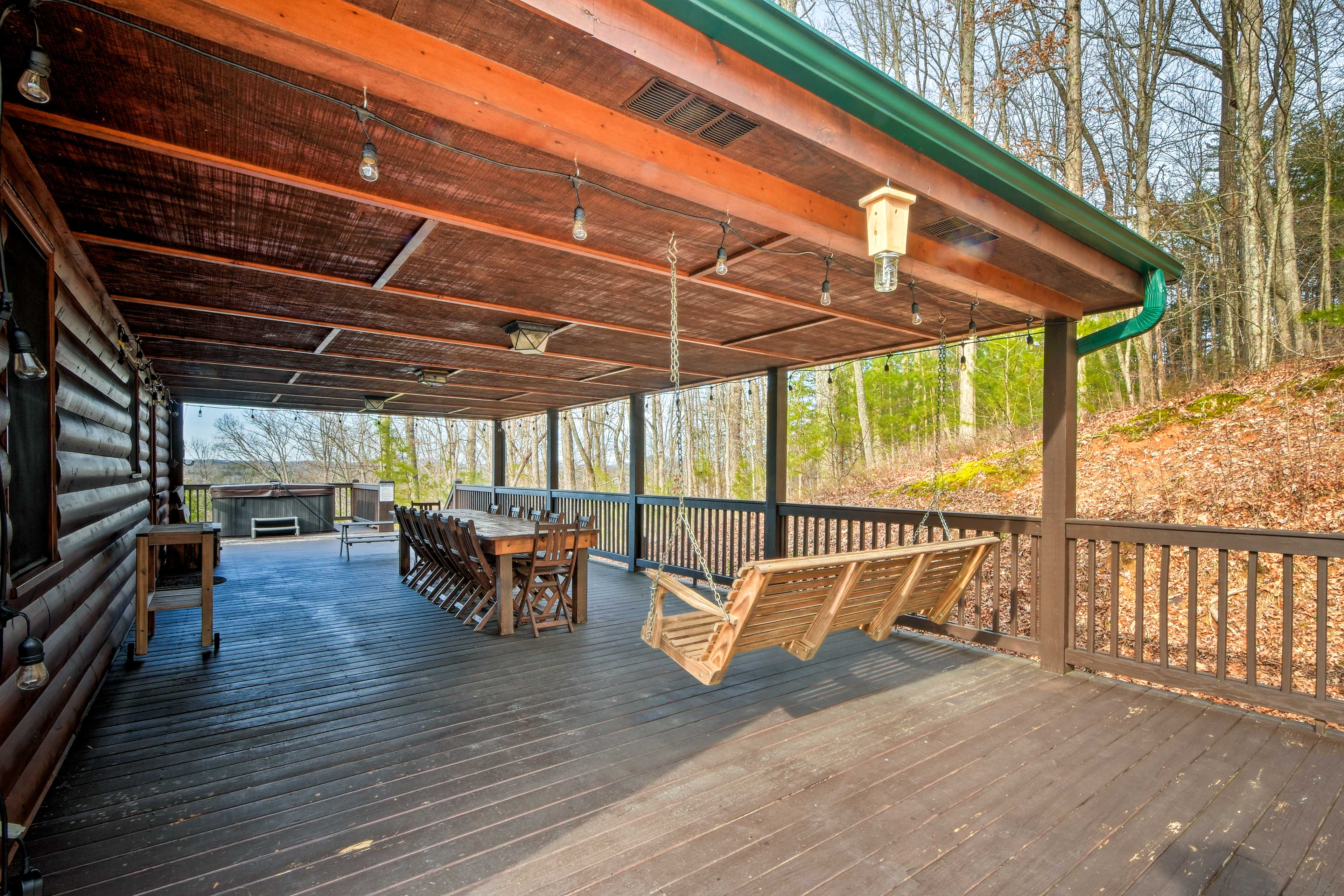 The deck boasts outdoor seating for everyone in addition to a wooden swing!