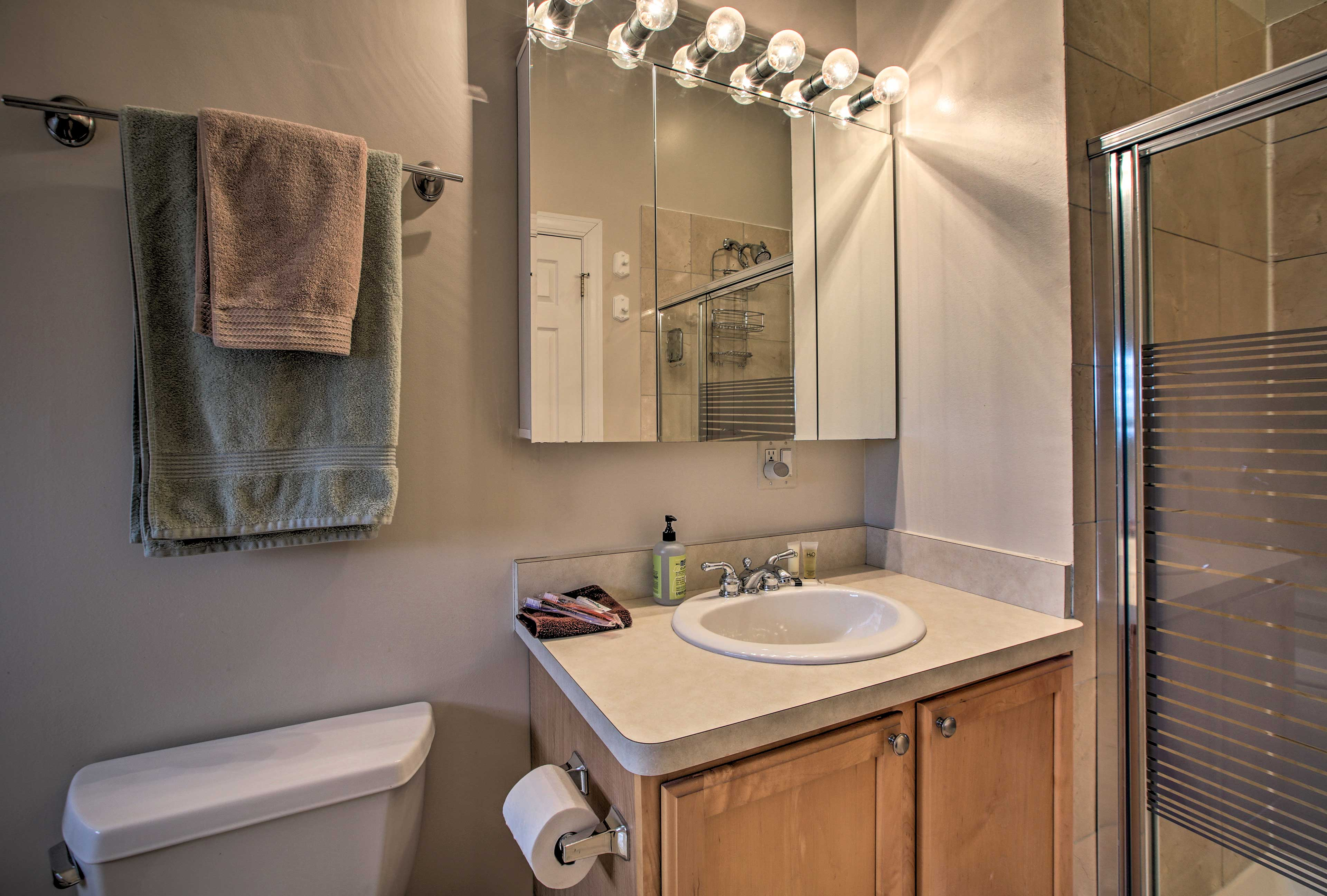 The first full bathroom features a walk-in shower with glass doors.