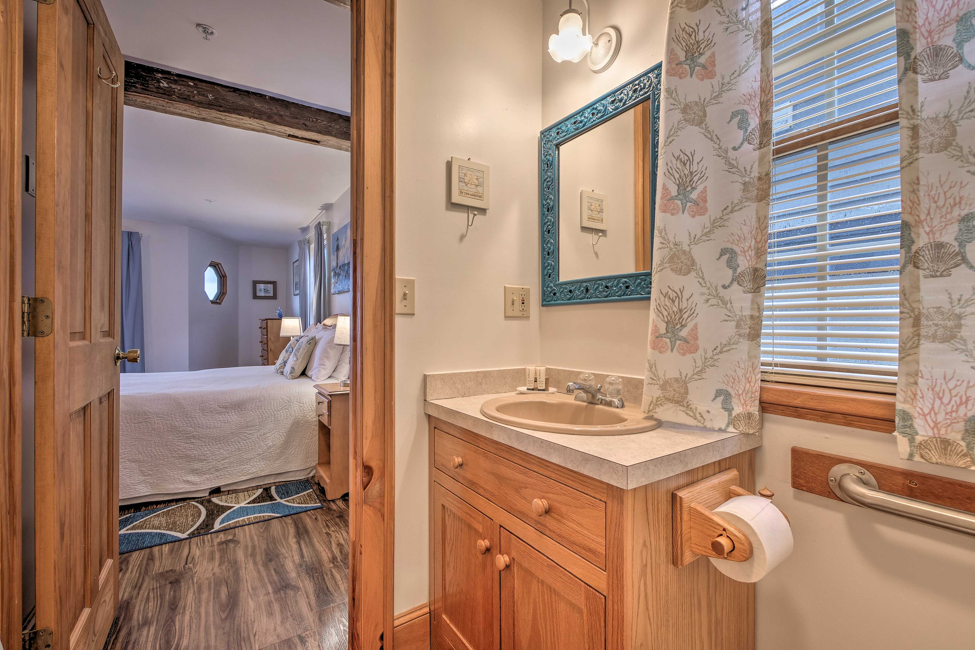 The bathroom is located just past the queen bed.