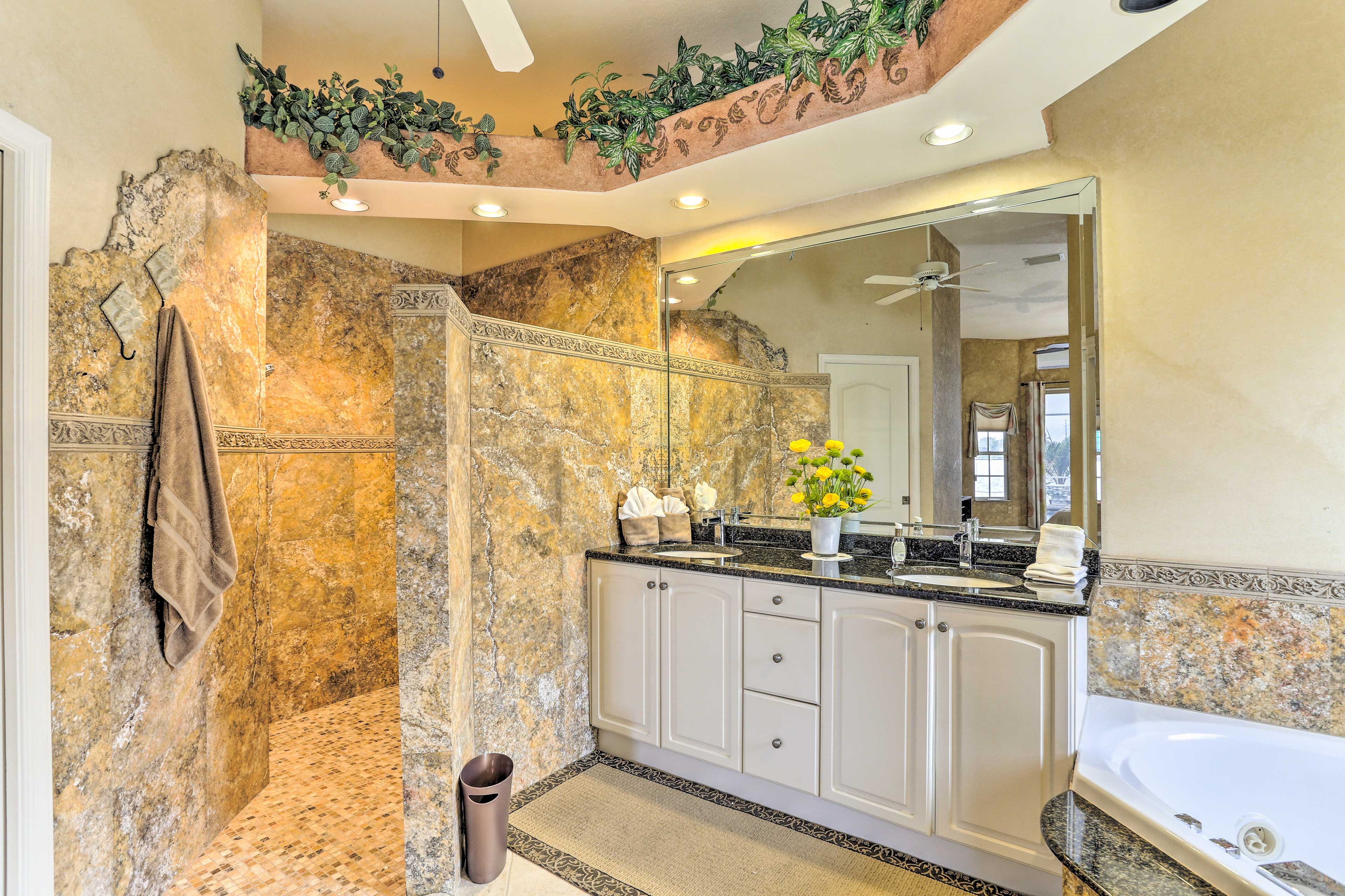 The en-suite bathroom boasts a custom shower with unique tiling.
