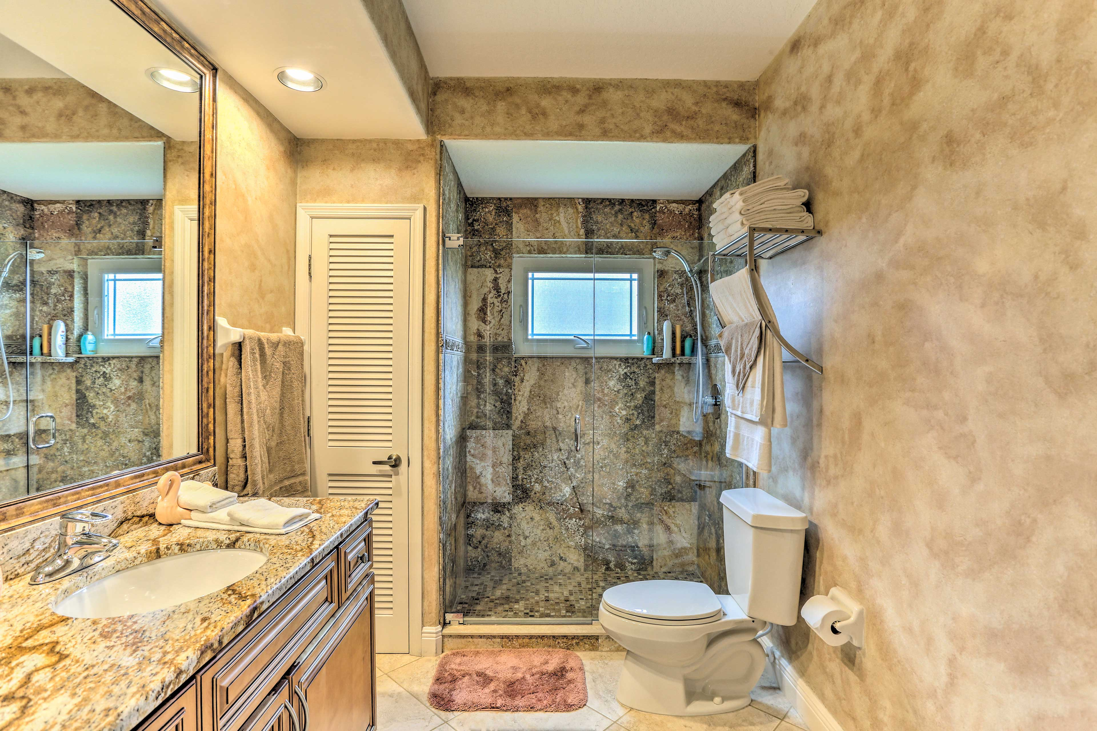 This full bathroom boasts custom tile work and a walk-in shower.