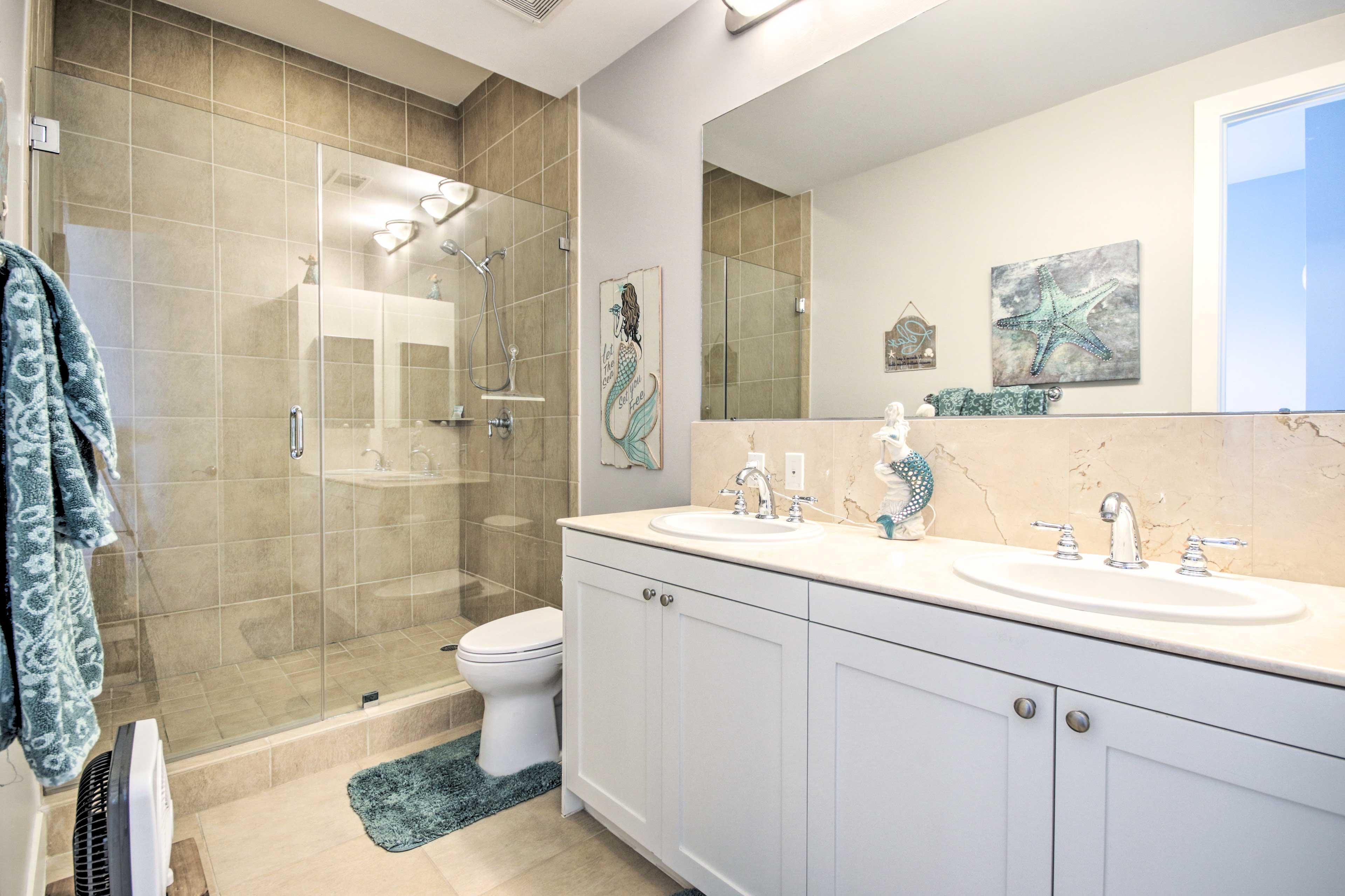 The en-suite bathroom has dual sinks and tile-filled shower.
