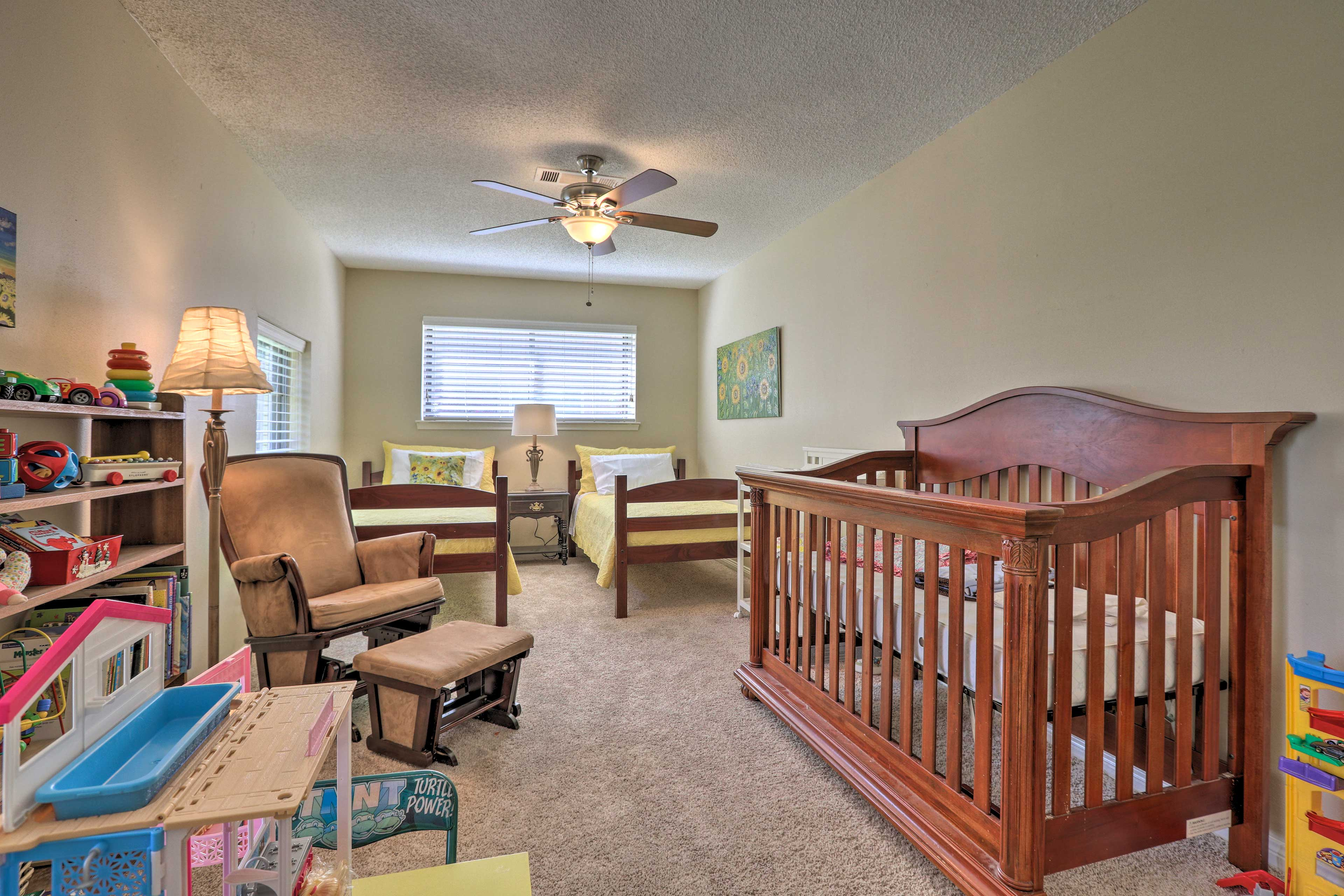 This bedroom features 2 twin beds and a crib.