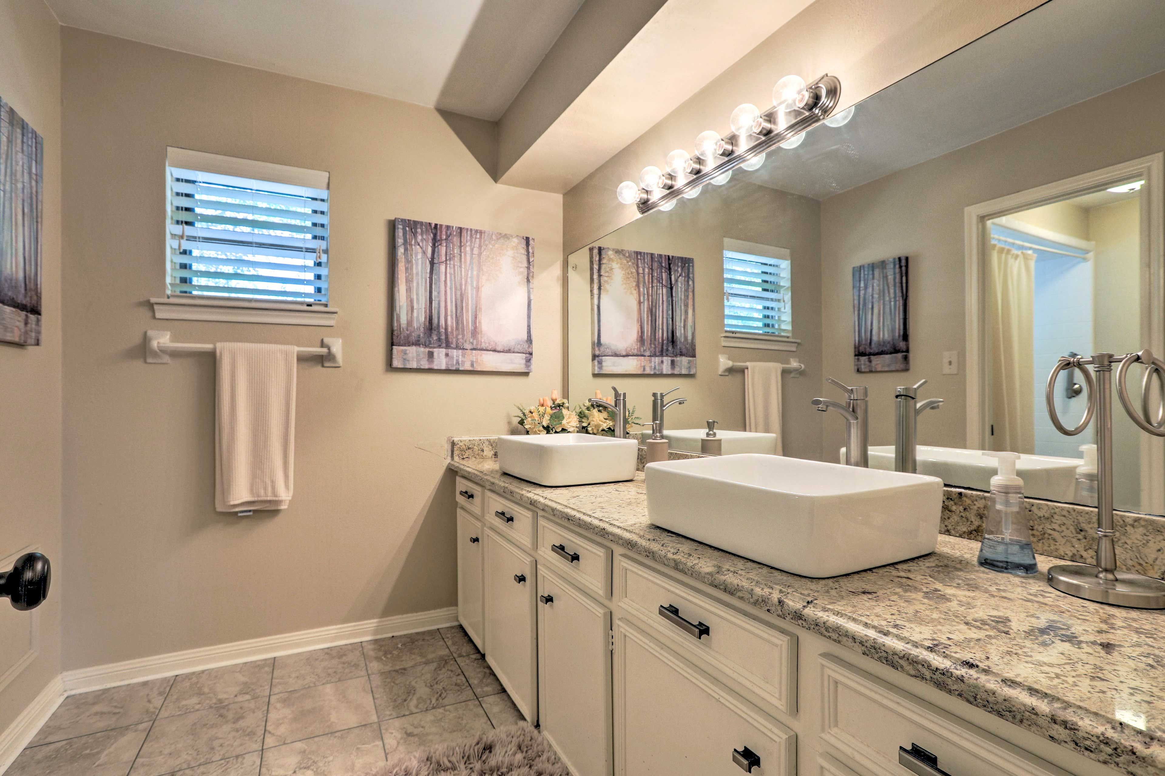 This bathroom includes a large vanity with double sinks.