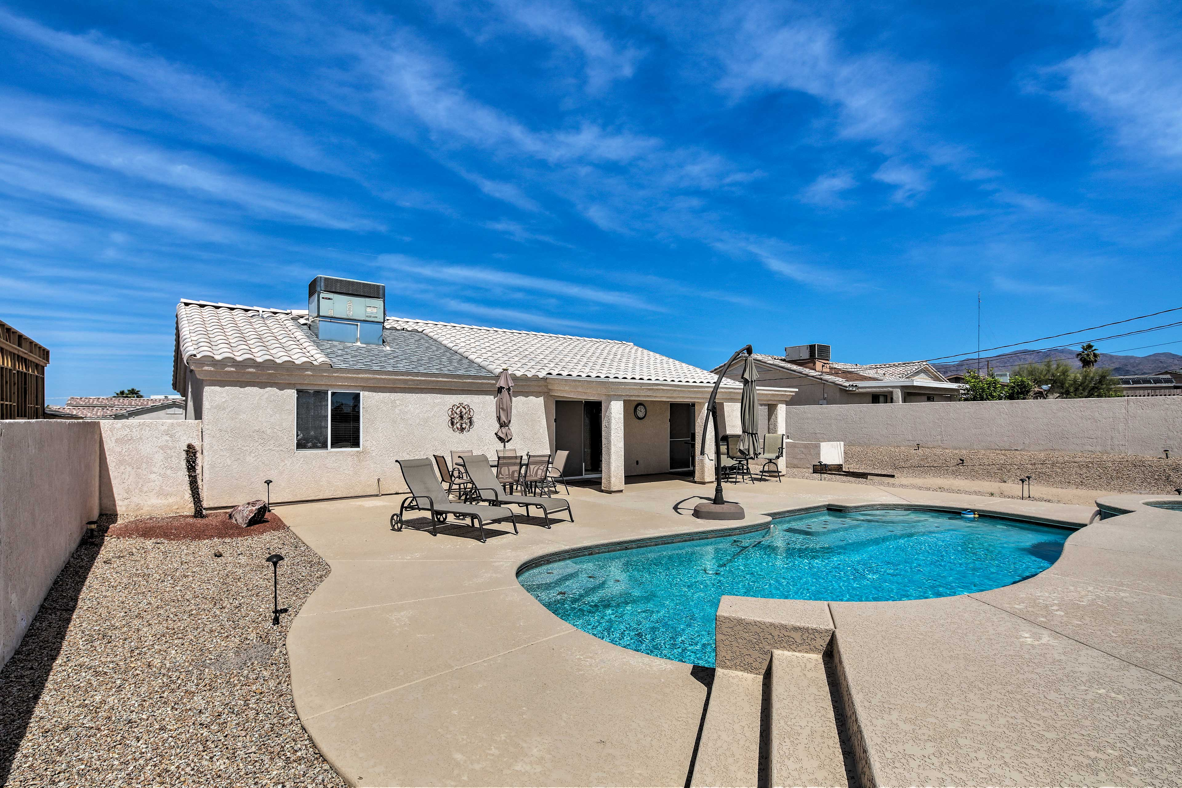 The pool and hot tub include a waterfall feature and stunning mountain views.