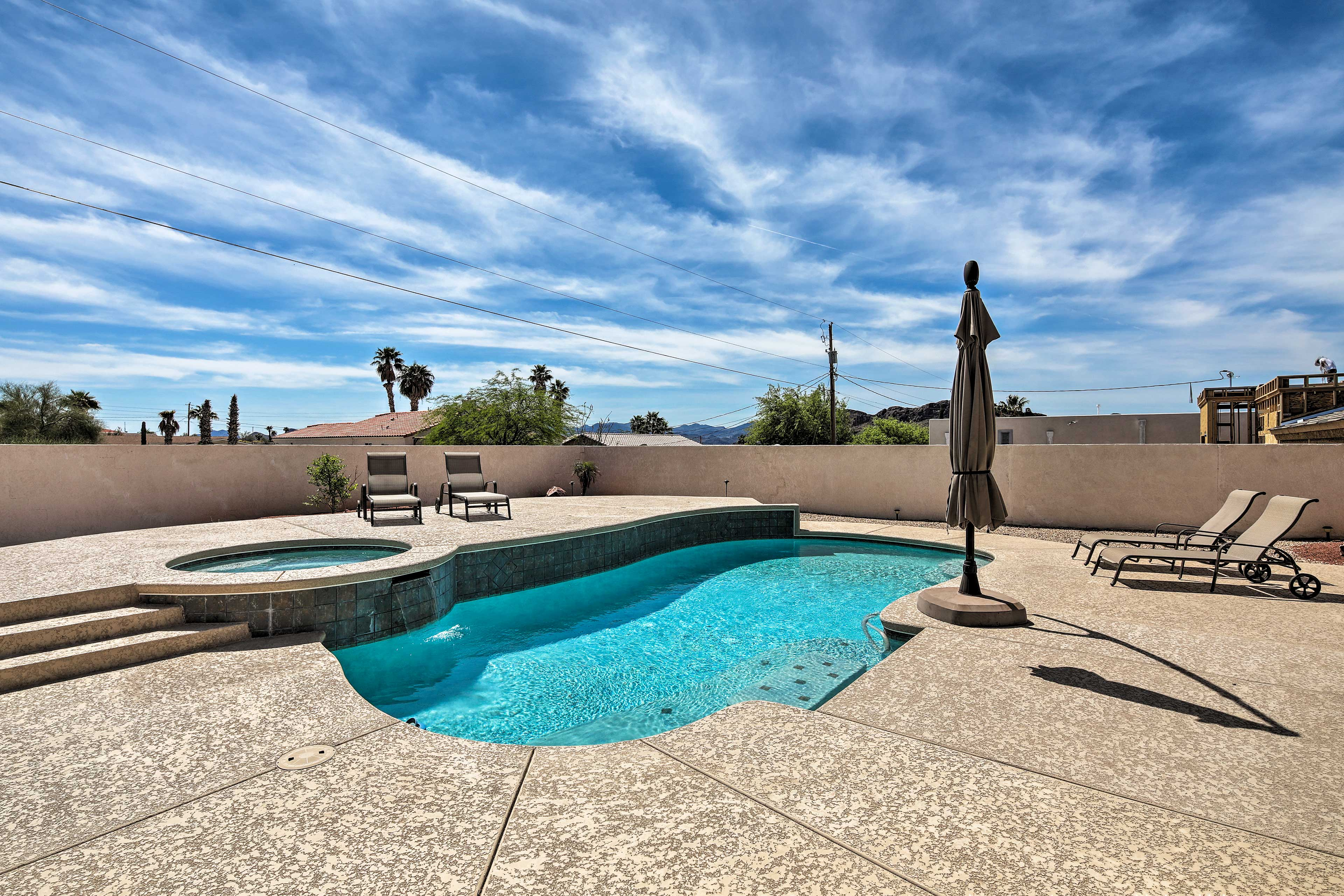 The vacation rental boasts a private pool, hot tub, patio, grill, & more!