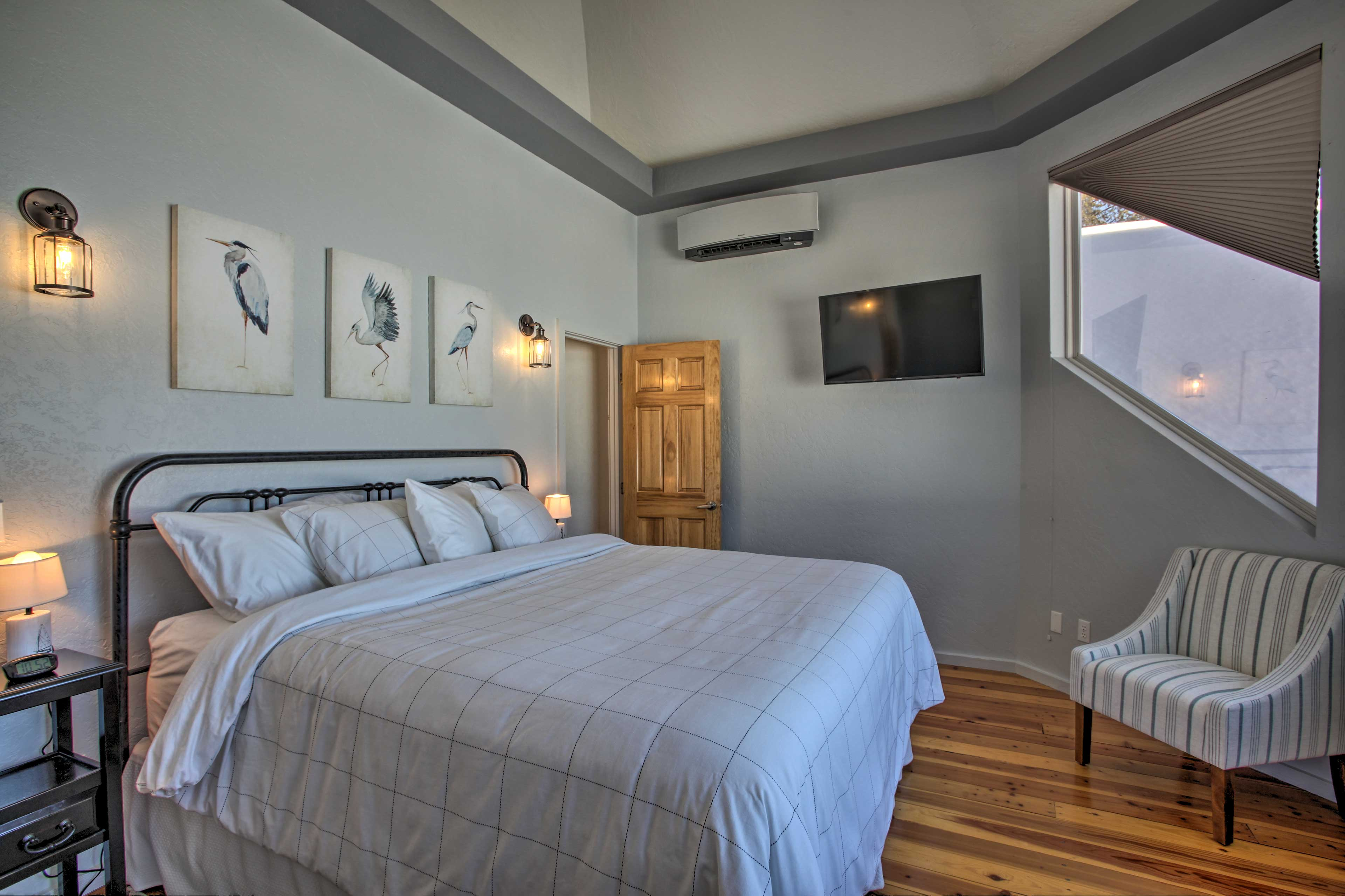 The master bedroom houses a king-sized bed and Smart TV.