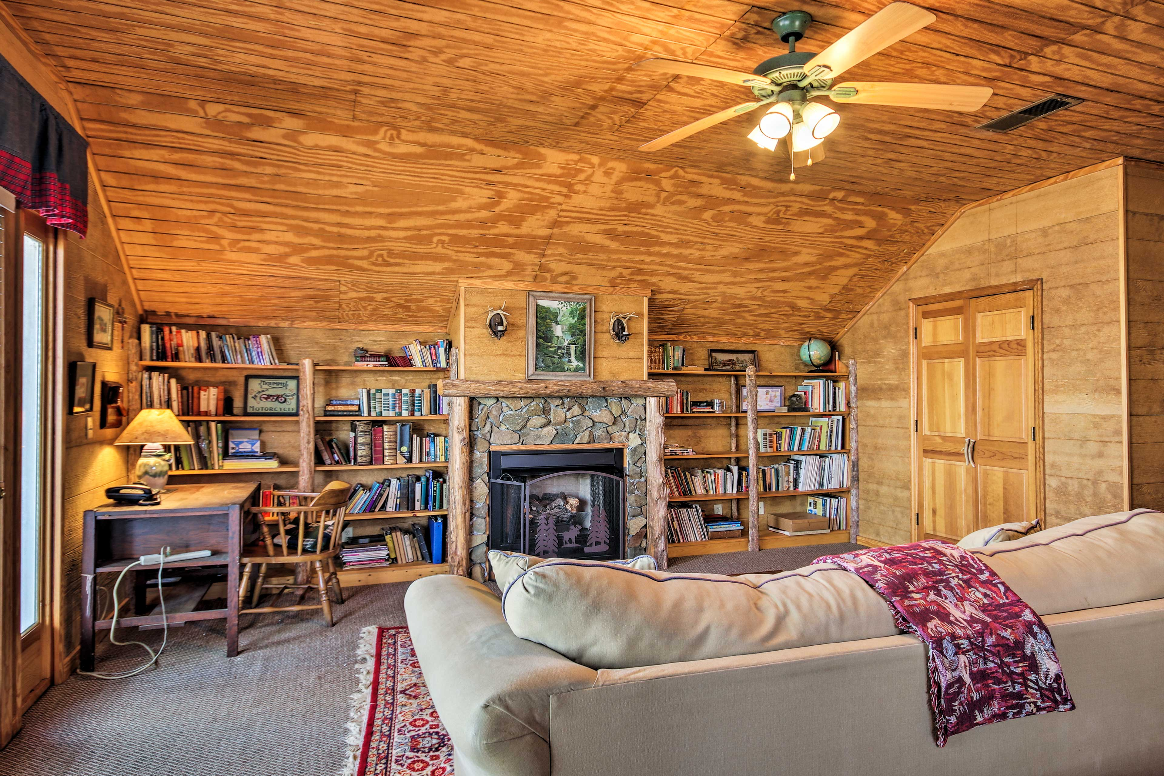 The master bedroom has a fireplace, desk, and a collection of books.