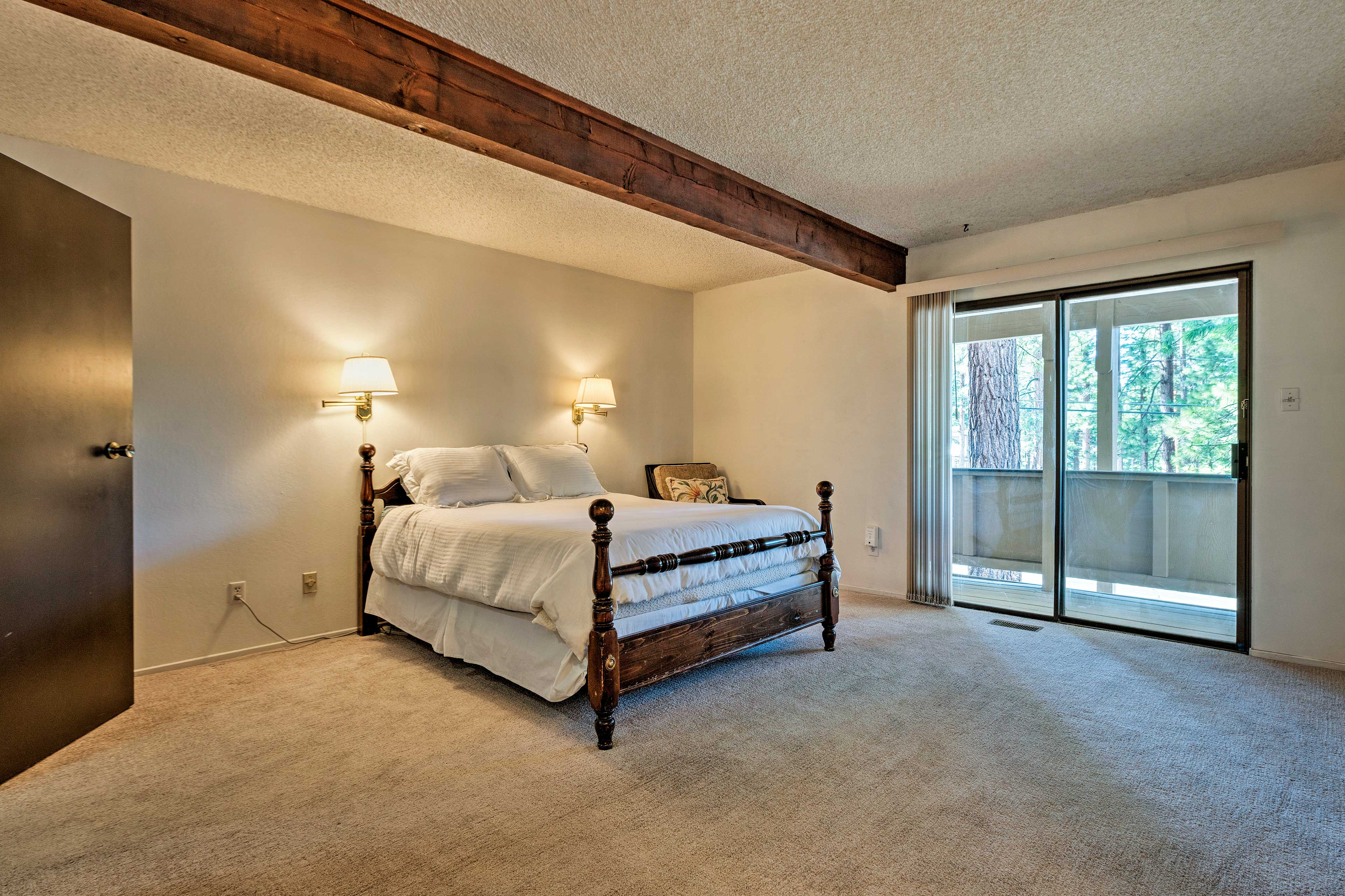 The master bedroom boasts a queen bed and access to the deck.