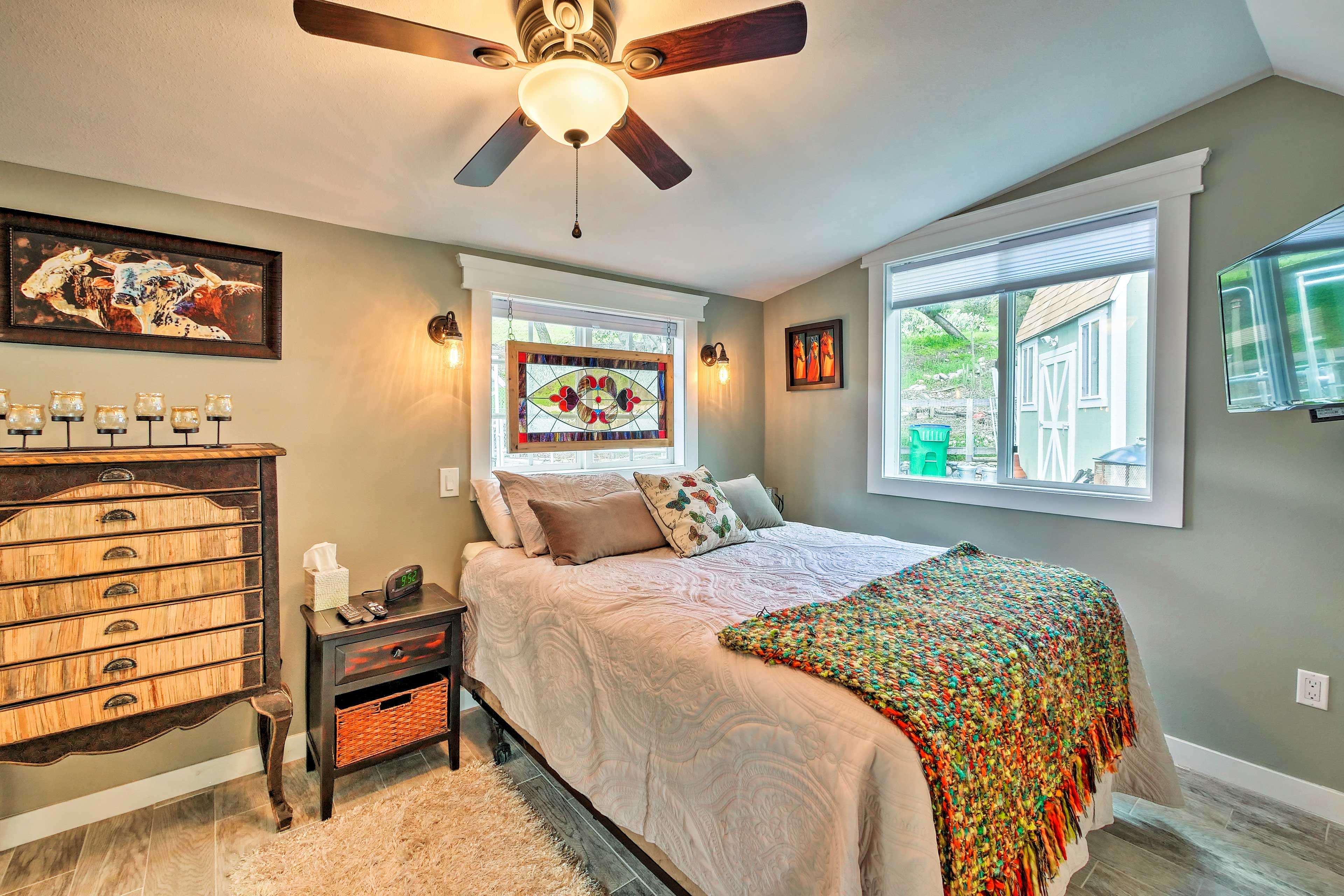 The vibrant and charming bedroom features a queen bed.