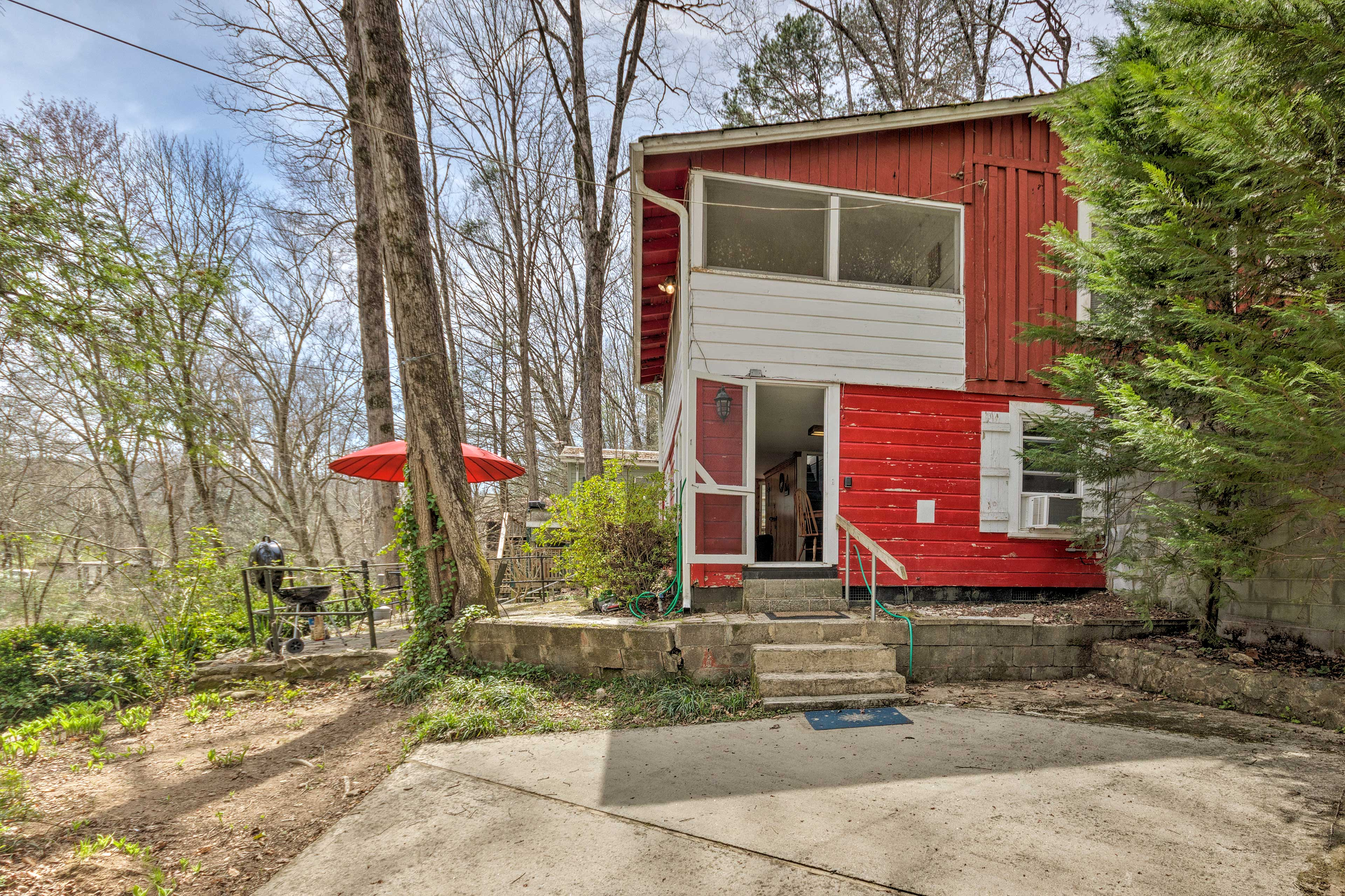 The 3-bedroom, 1.5-bathroom home has a sunporch and lush forest surroundings.