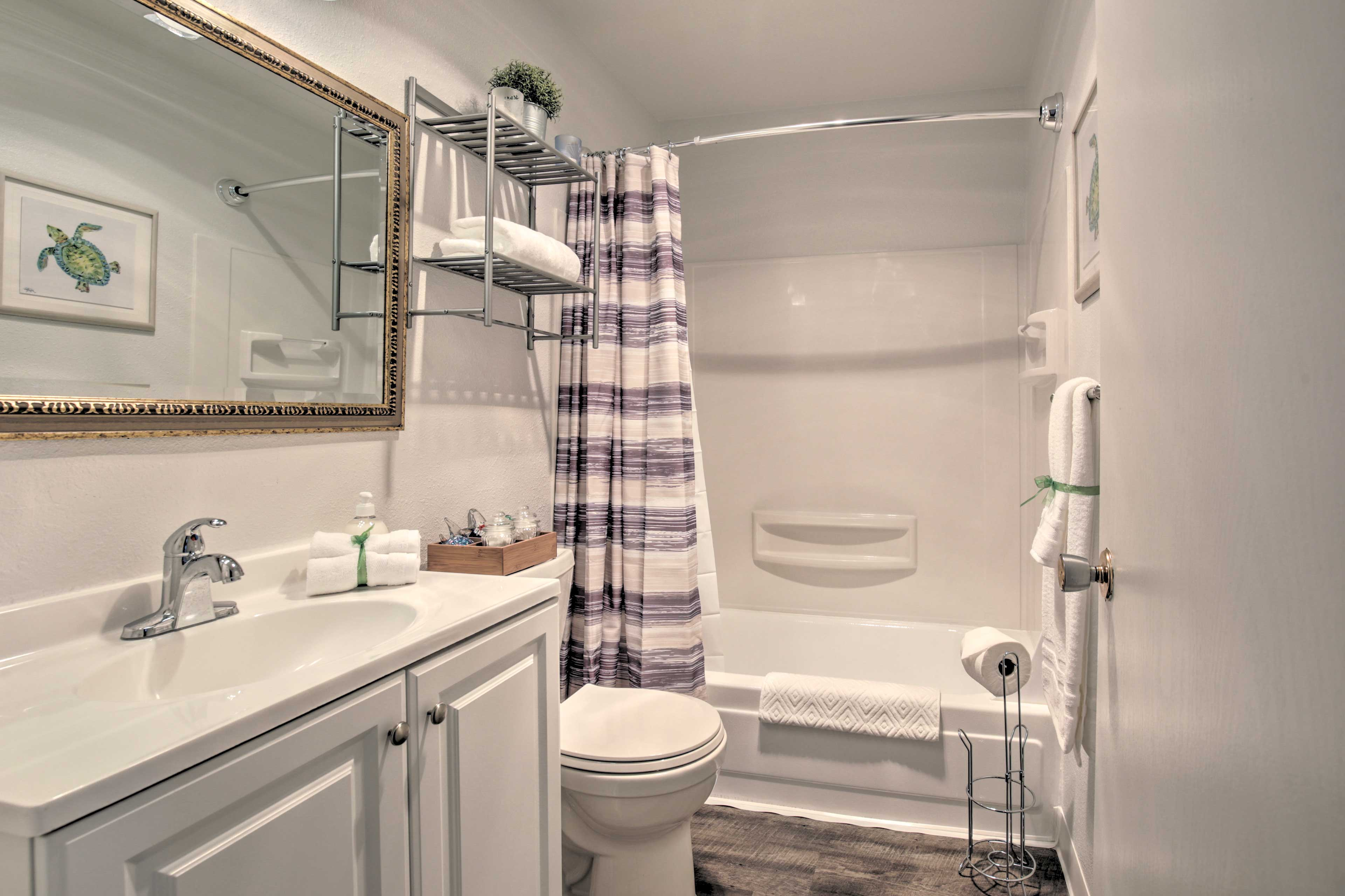 The bathroom includes a shower/tub combo & complimentary toiletries.