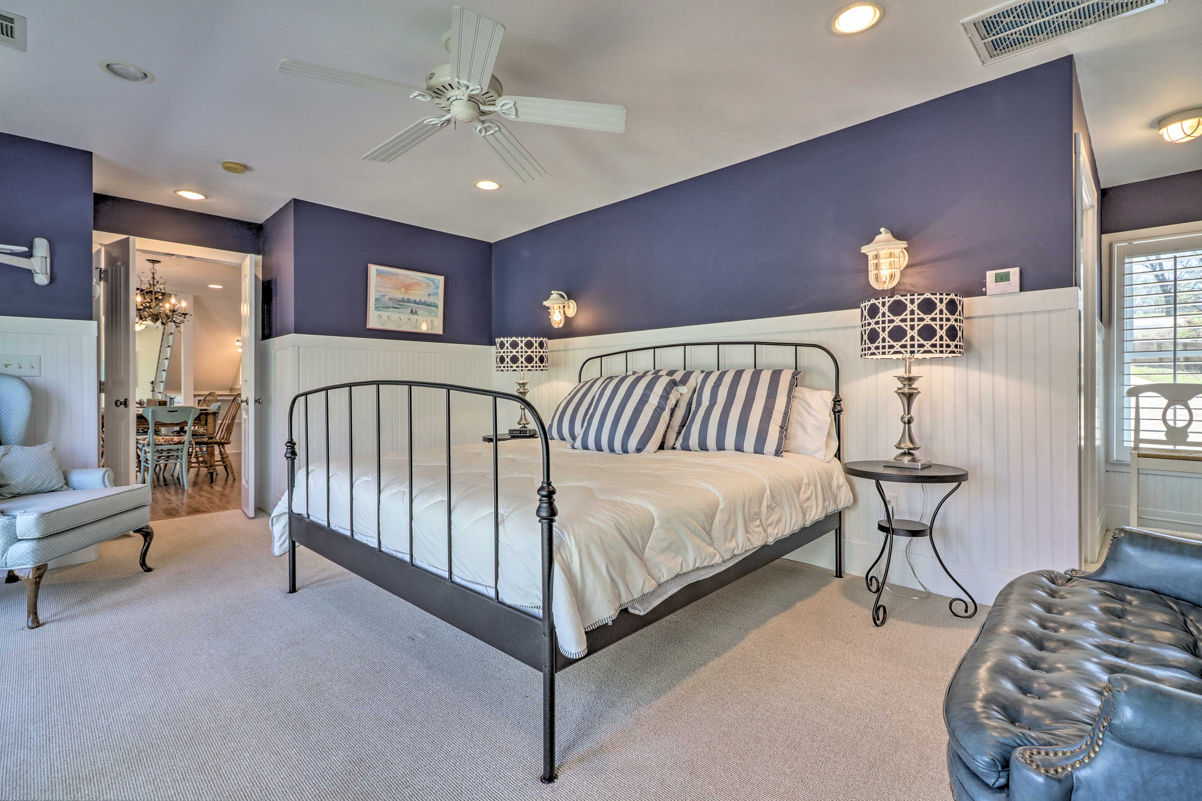 Nautical sconces frame the king-sized bed with warm light.