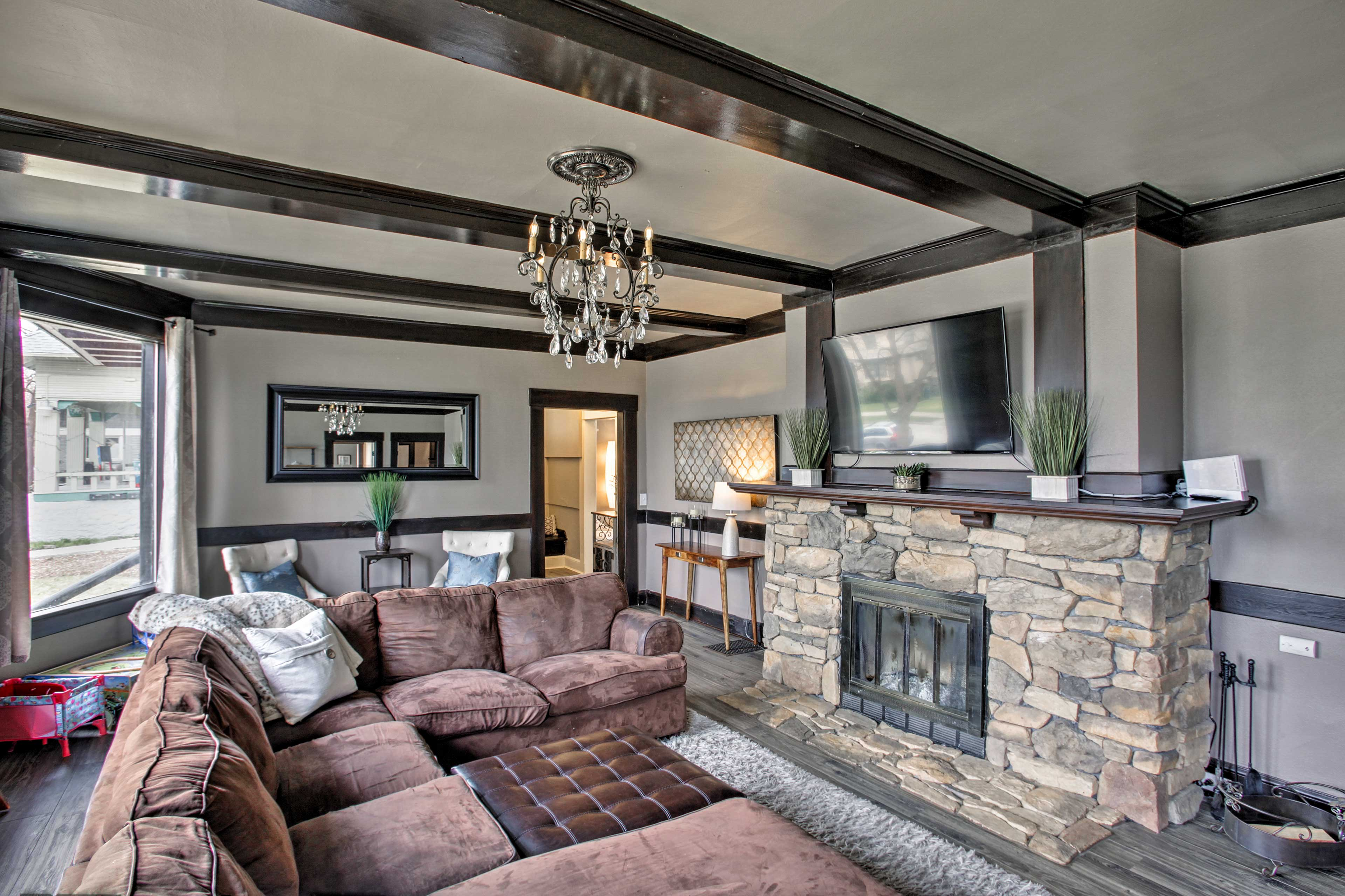 The large living area features a wood-burning fireplace and flat-screen TV.