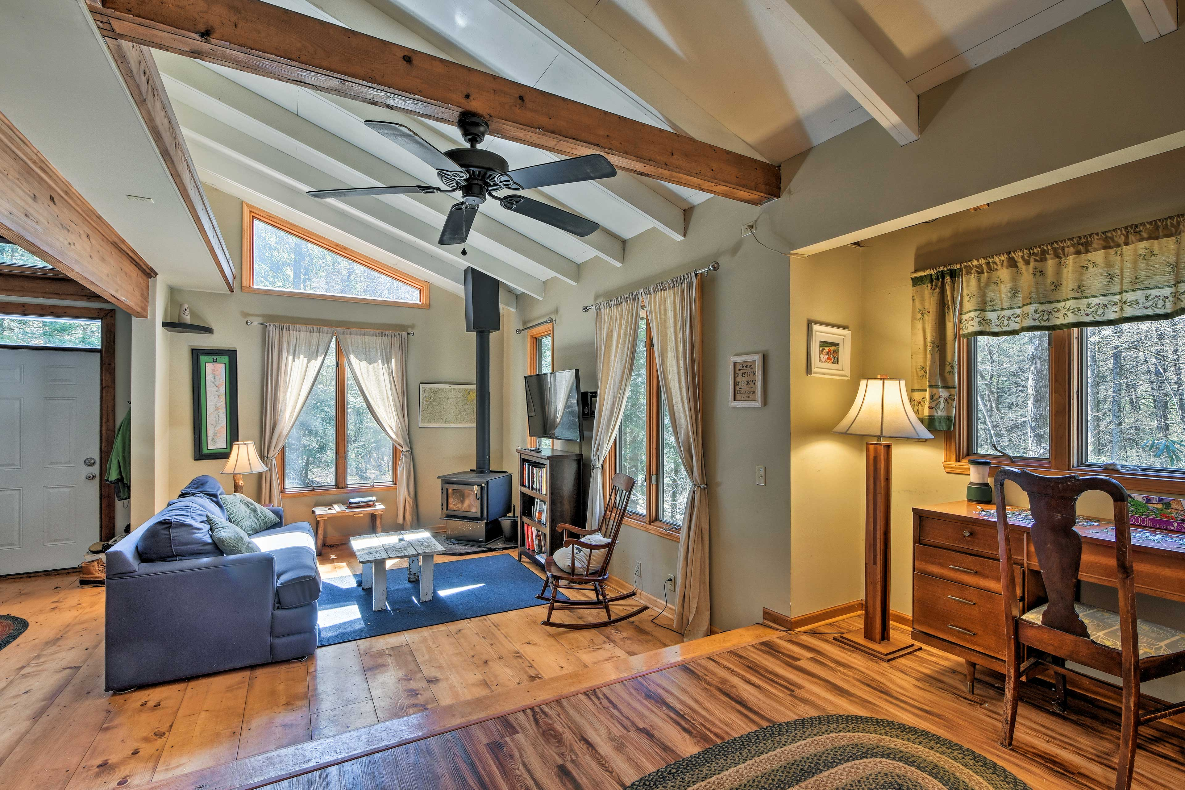 The living area features a flat-screen TV and wood-burning stove.