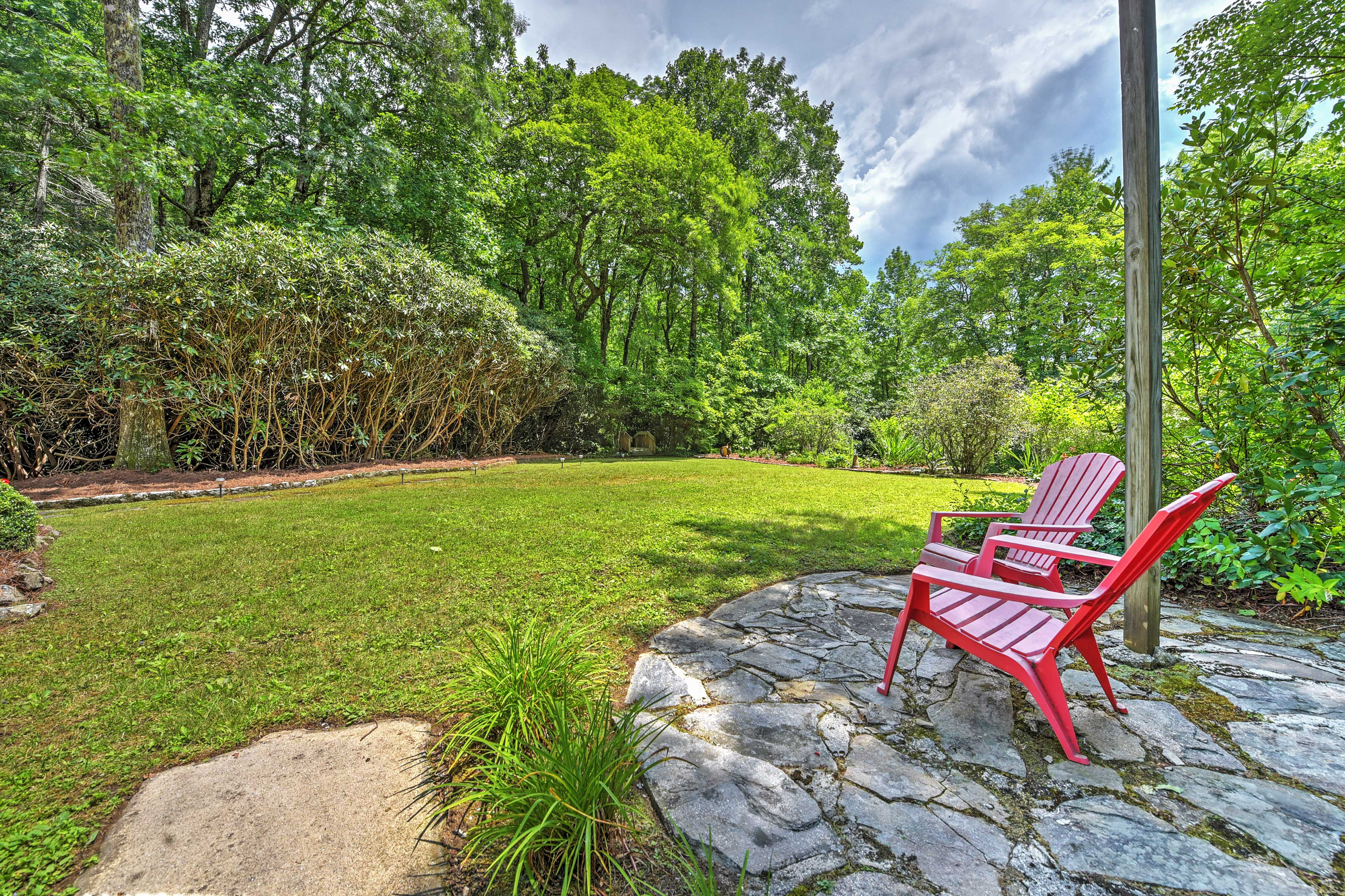 Adirondack chairs on the stone sitting area provide more seating.