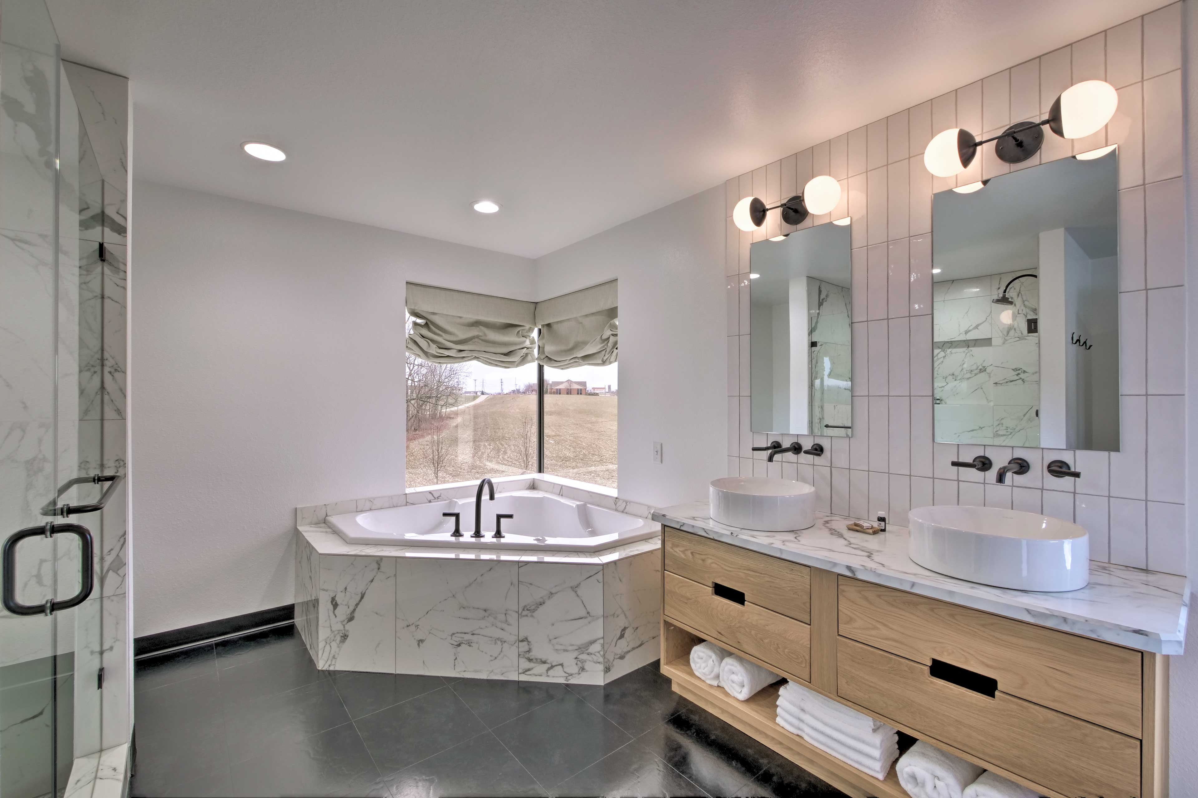 The en-suite bathroom includes a large soaking tub and walk-in shower.
