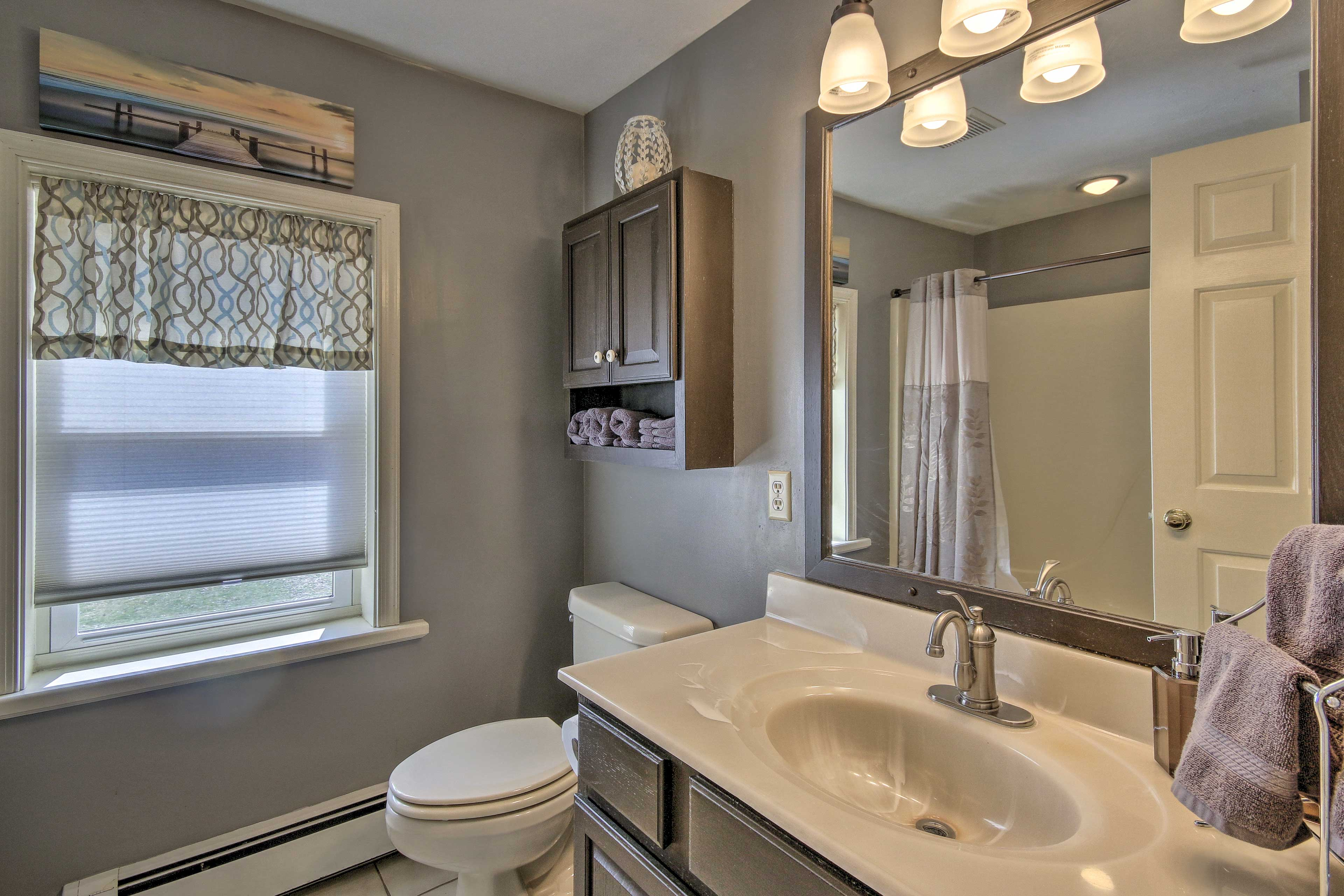 The full bathroom is stocked with fresh towels.