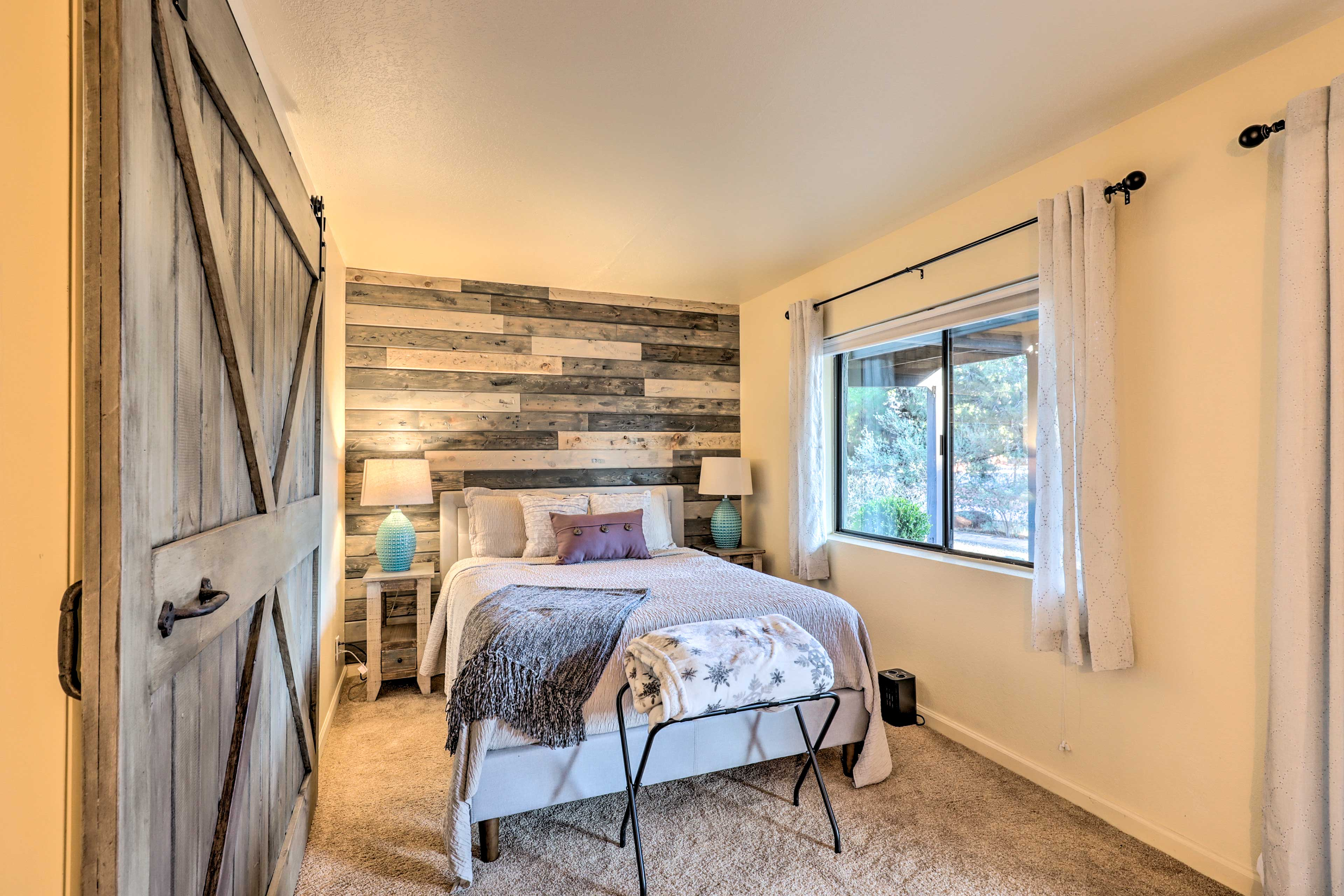 Bedroom 2 features a wood accent wall and a queen memory foam mattress.