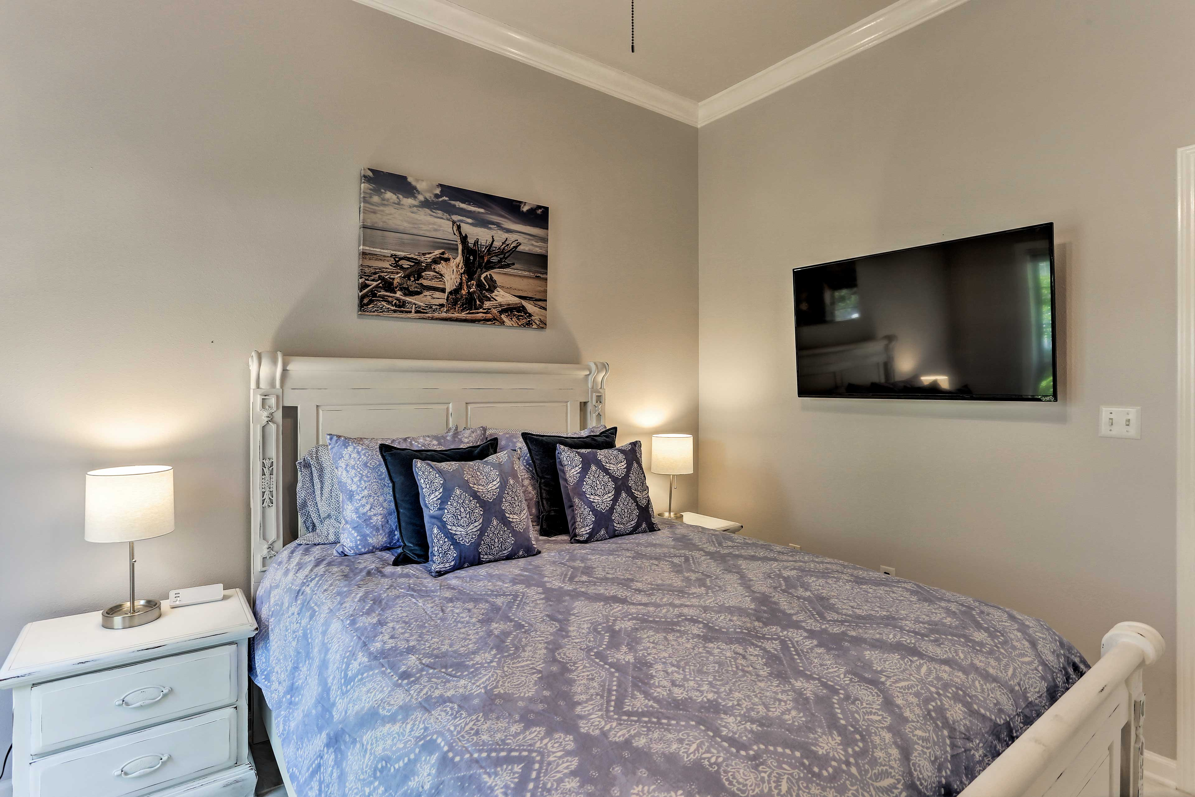 This bedroom features a queen bed & mounted Smart TV.