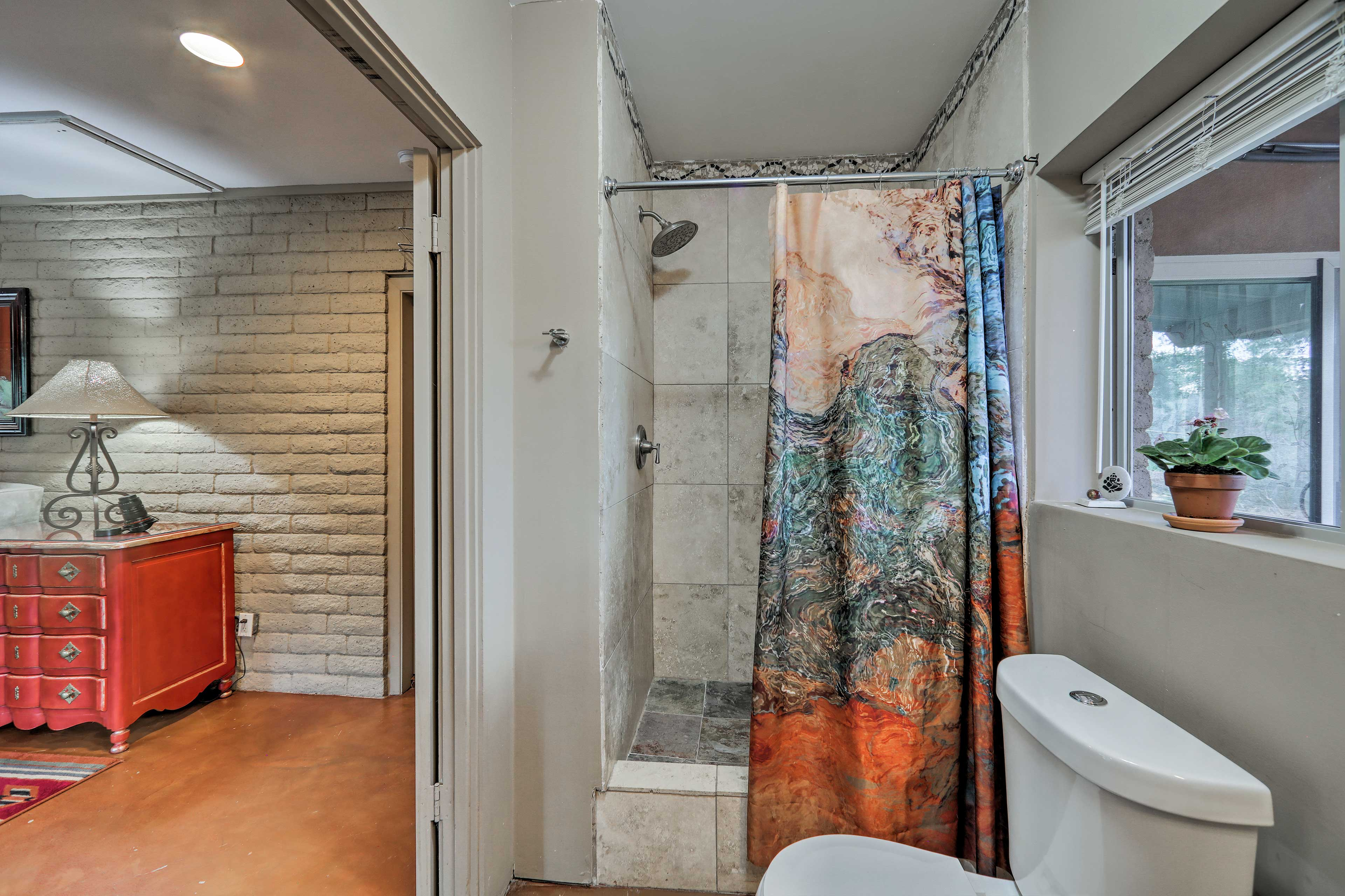 The full bathroom includes a sleek walk-in shower.