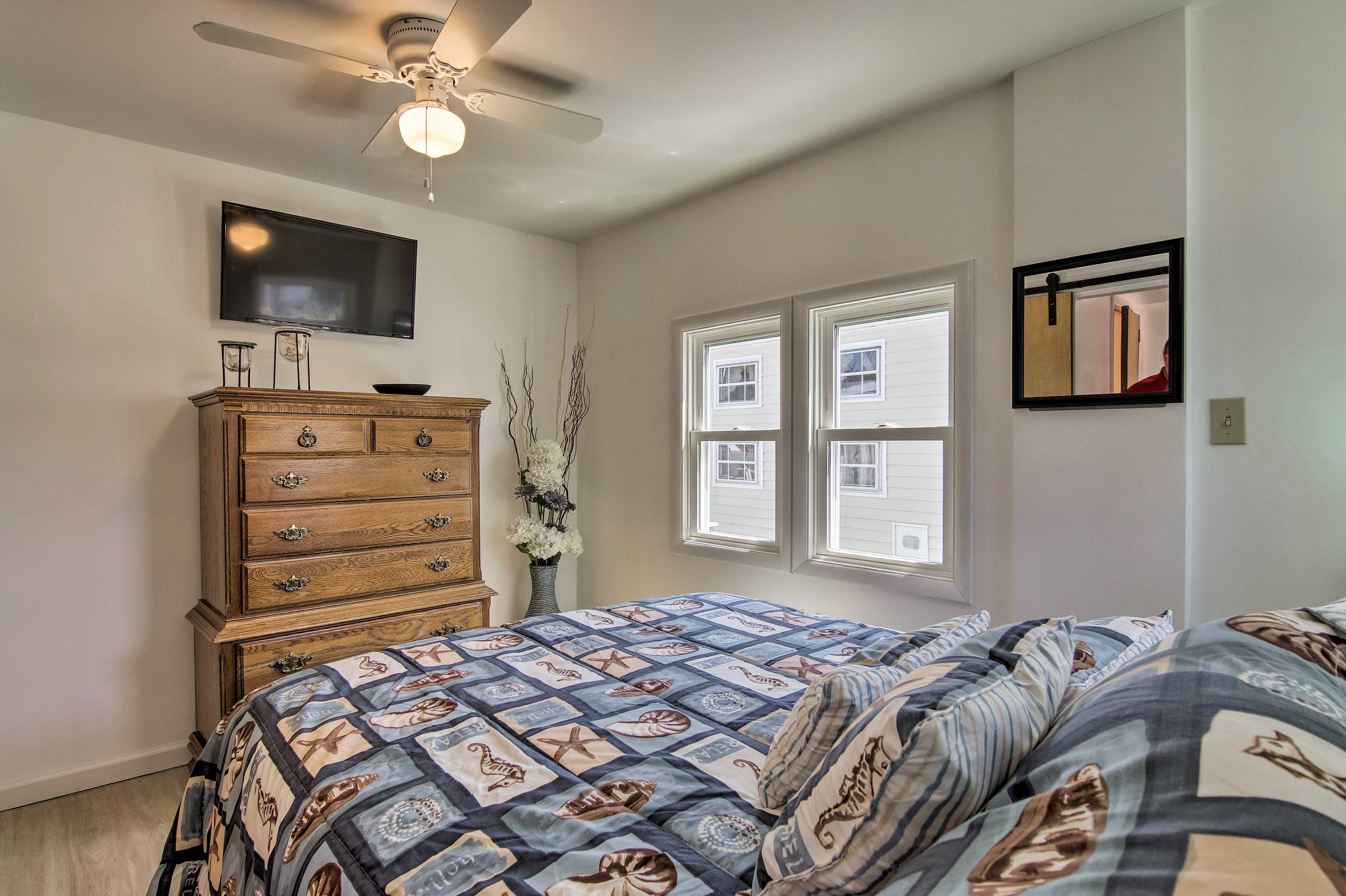 The first bedroom boasts a queen bed and mounted flat-screen TV.