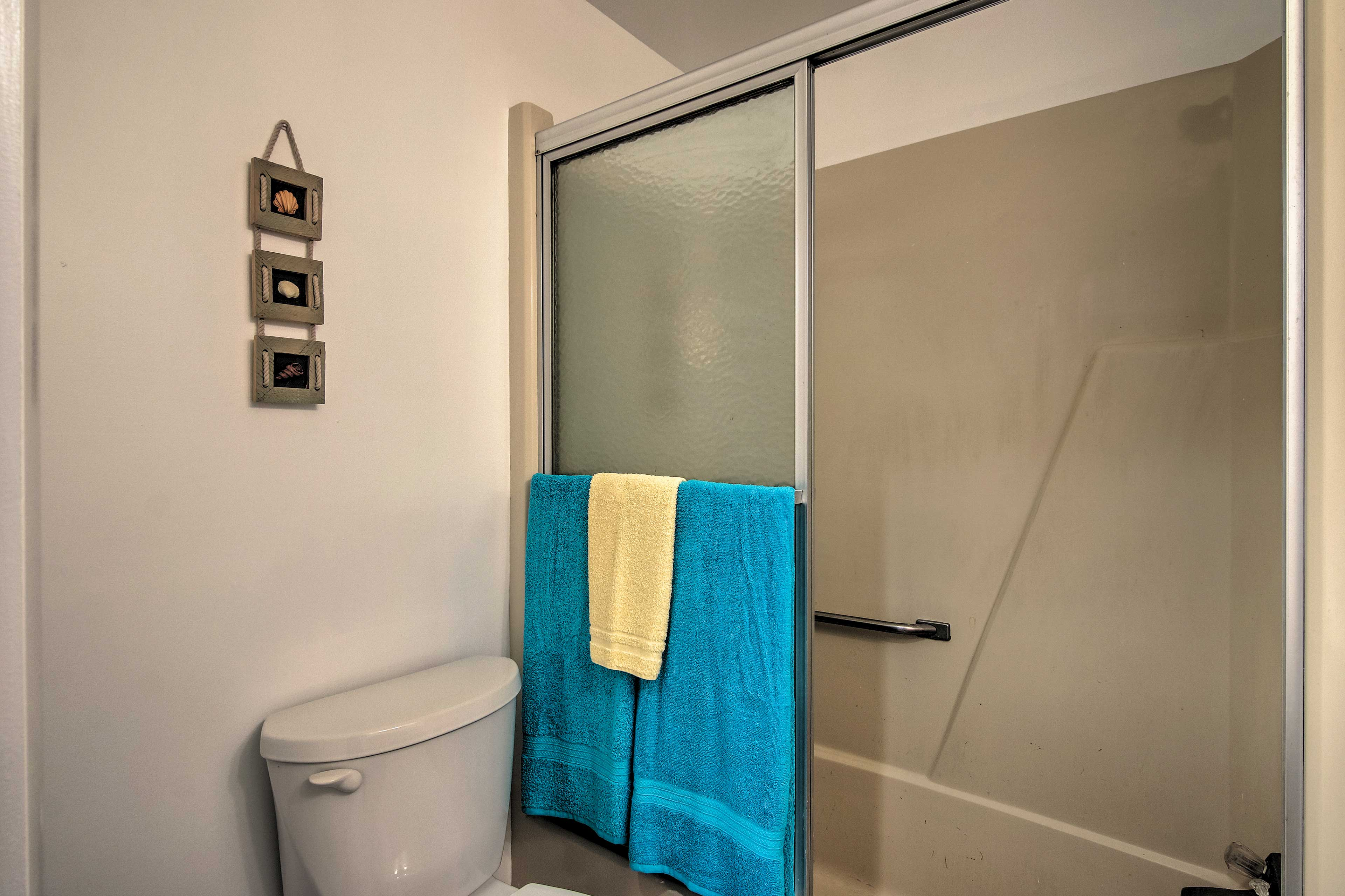 The bathroom includes a shower/tub combo with a glass door.