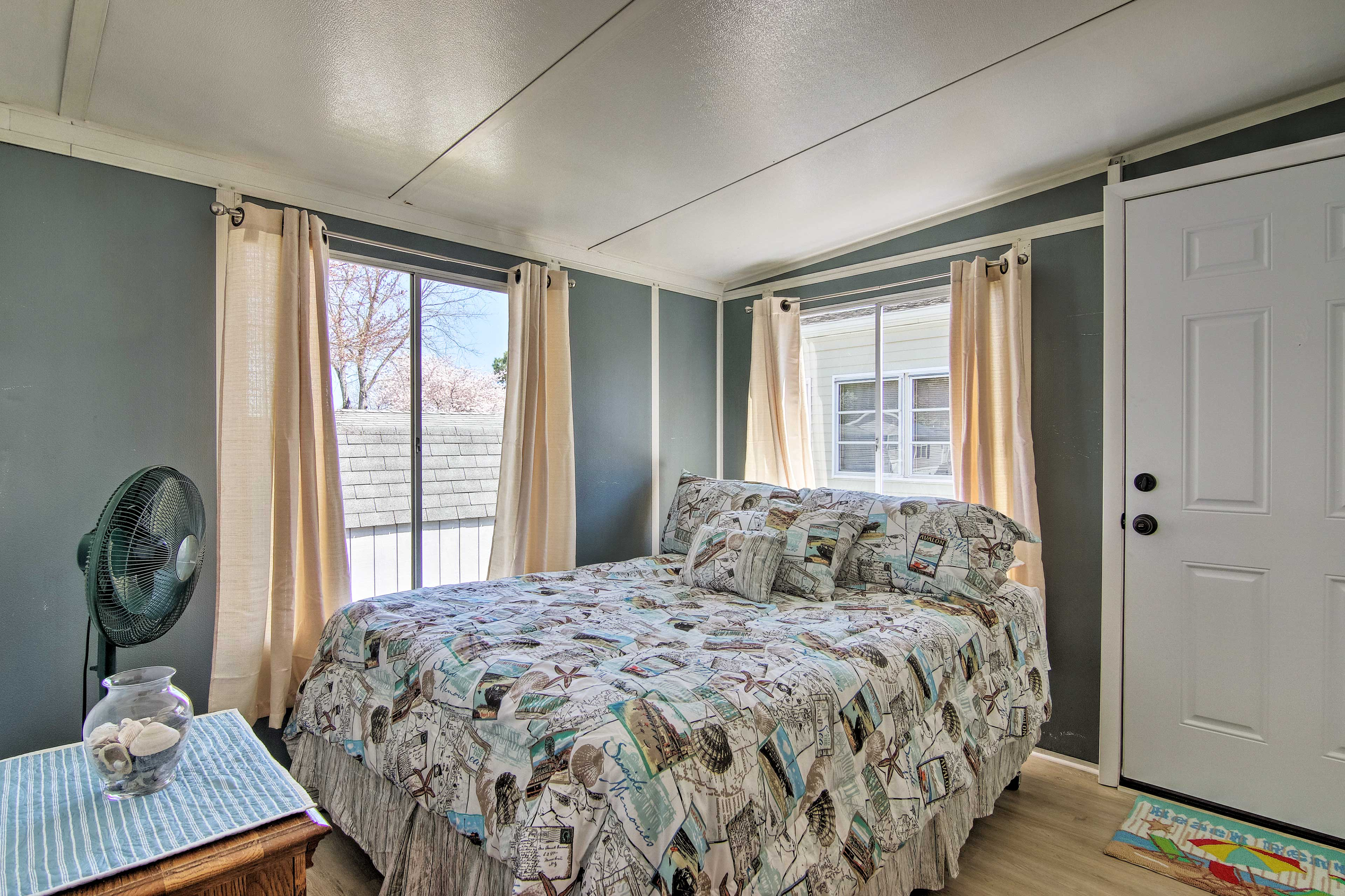 The 2nd bedroom includes a queen bed and standing fan for summer nights.