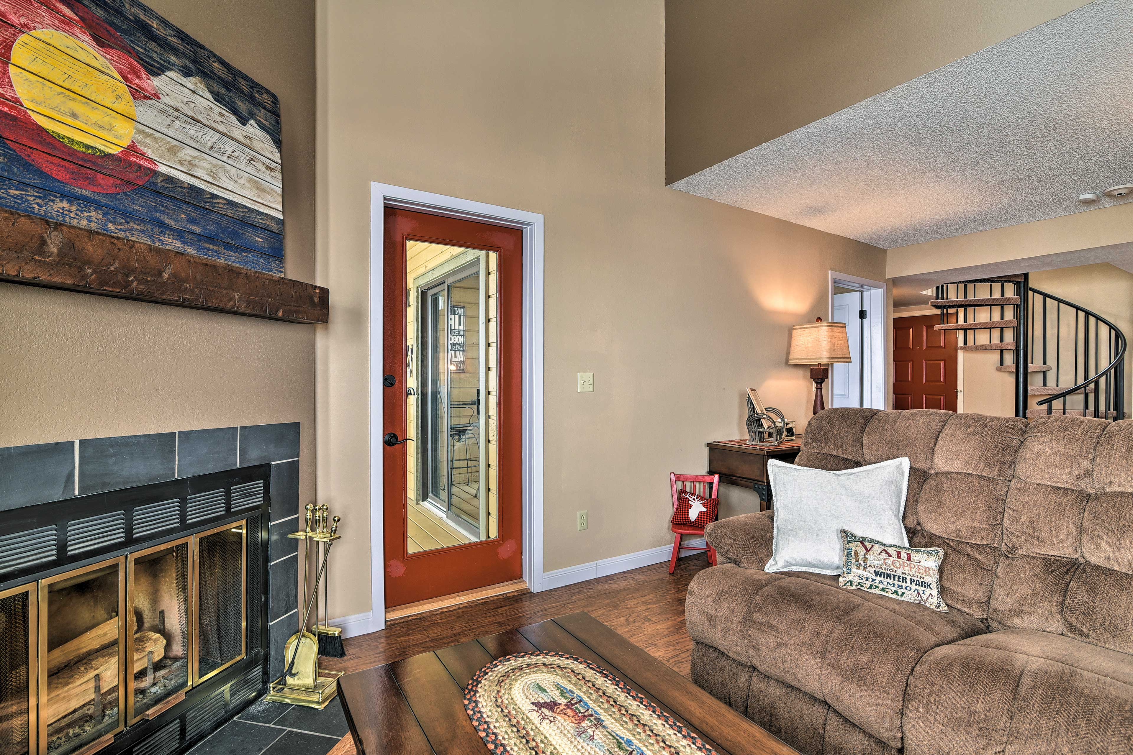 Neighboring the fireplace is a Smart TV and a door to access the balcony.