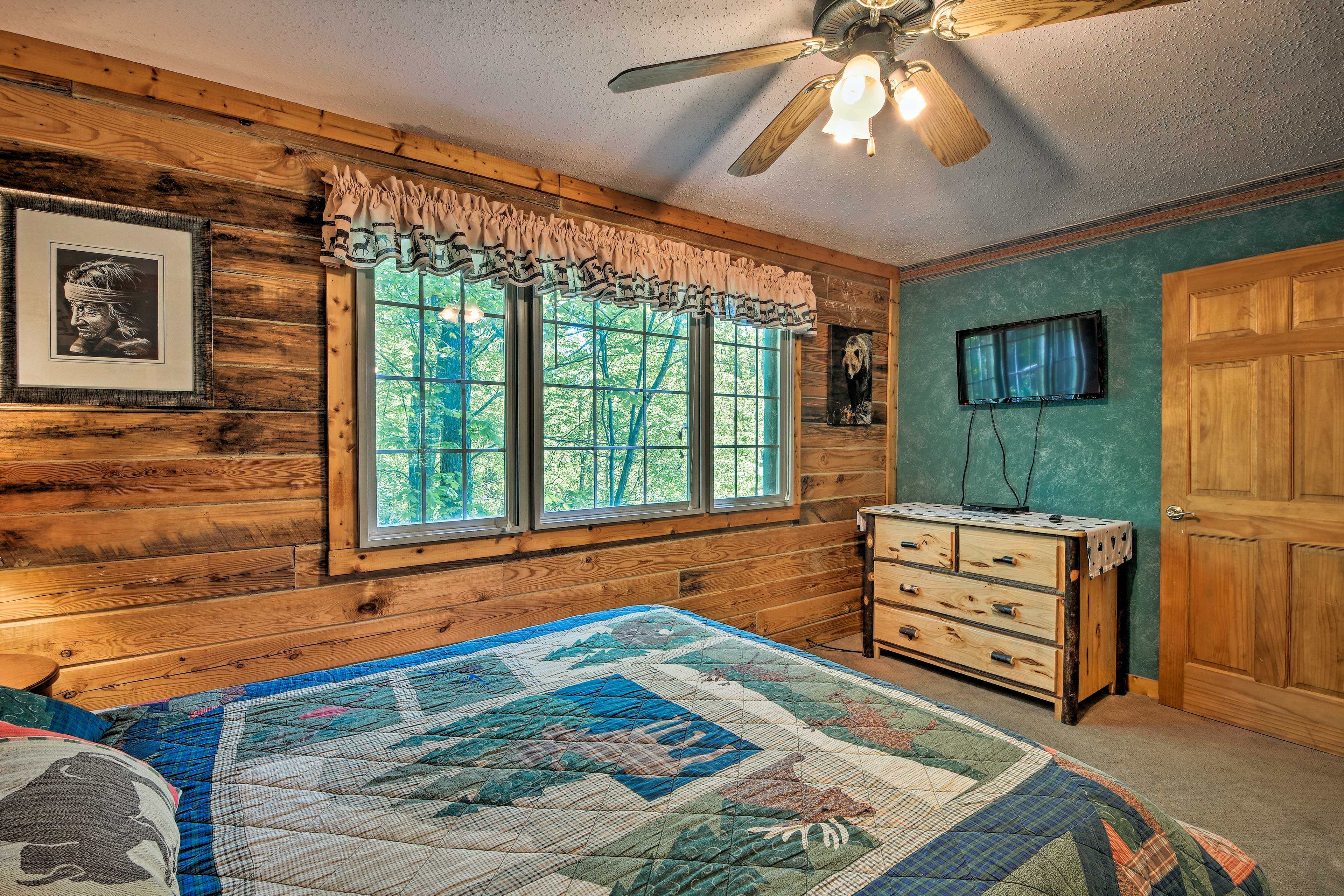 This bedroom also features amenities like a flat-screen TV and dresser.