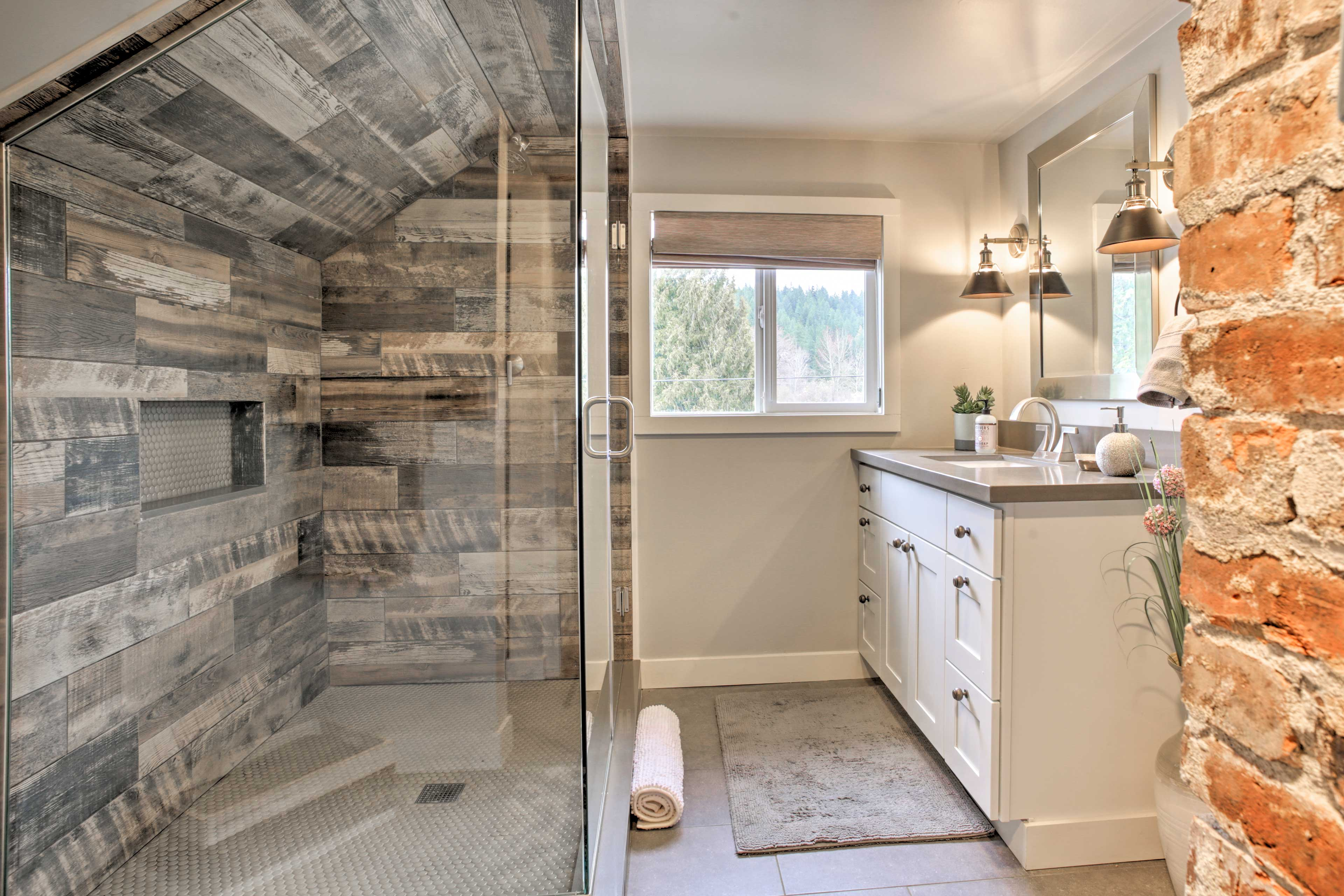 Rustic brick gives way to an elegant full bathroom with a glass-enclosed shower.