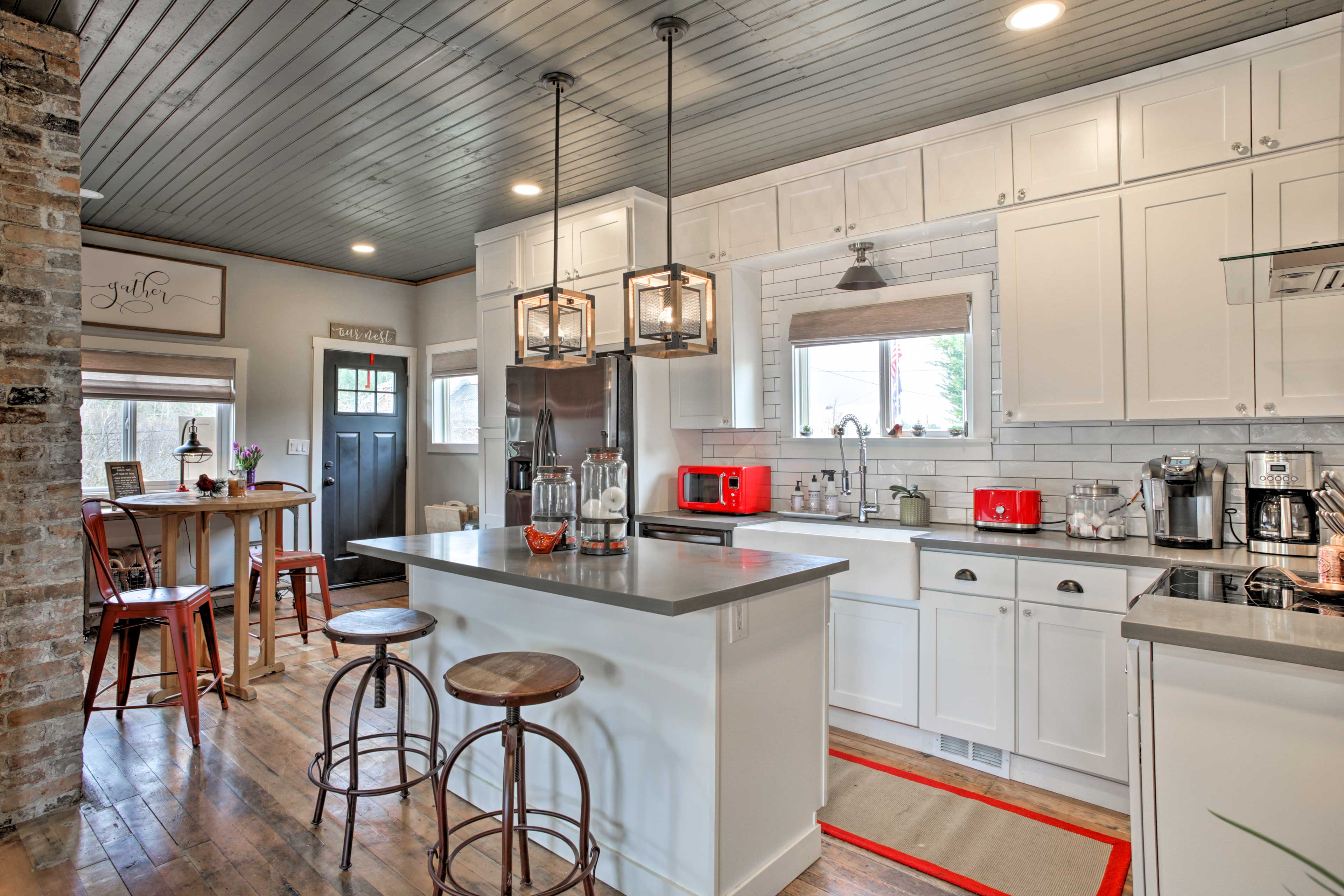 The sleek fully equipped kitchen boasts subway tile and a kitchen island.