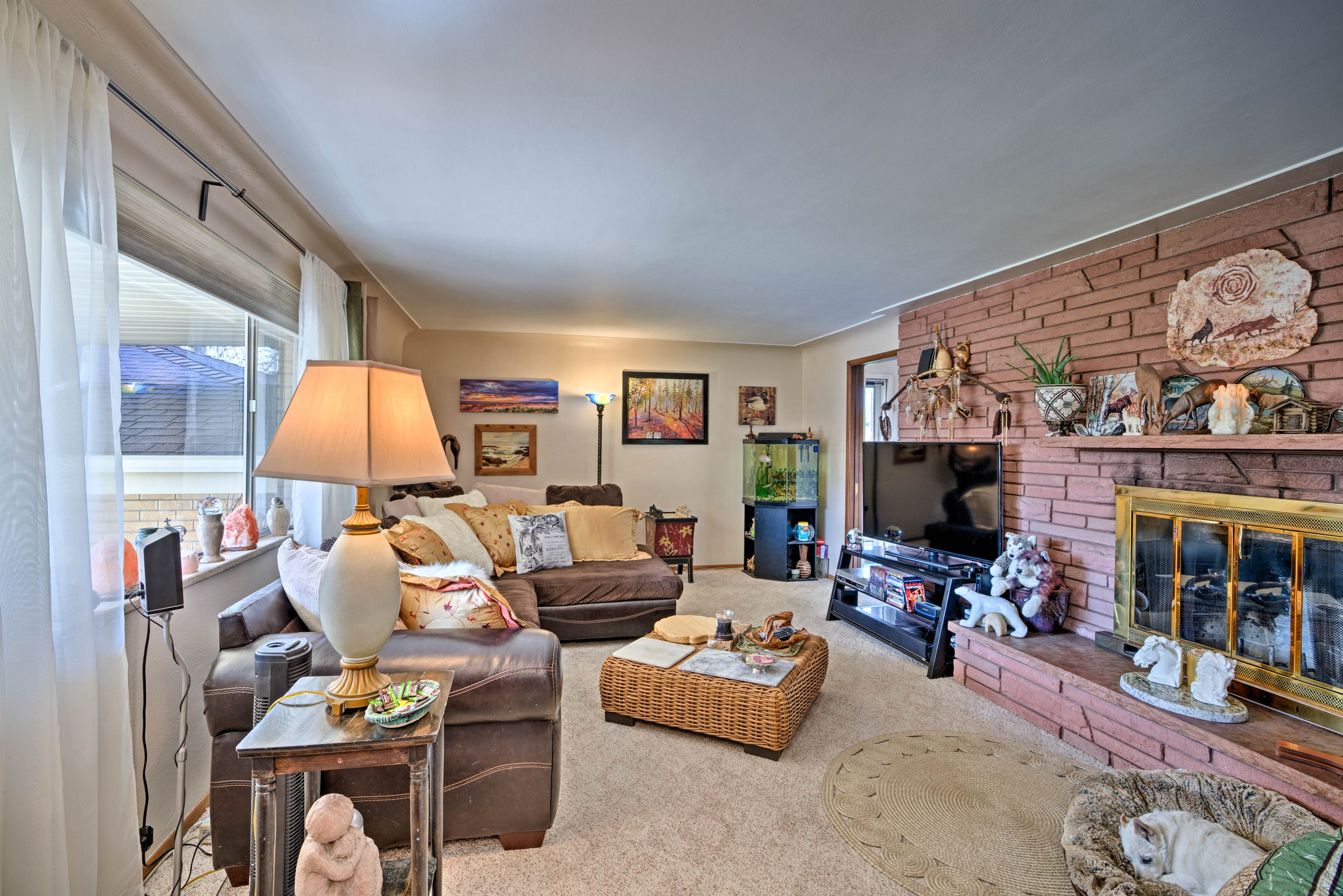 Brick accents and a large flat-screen TV highlight the living area.