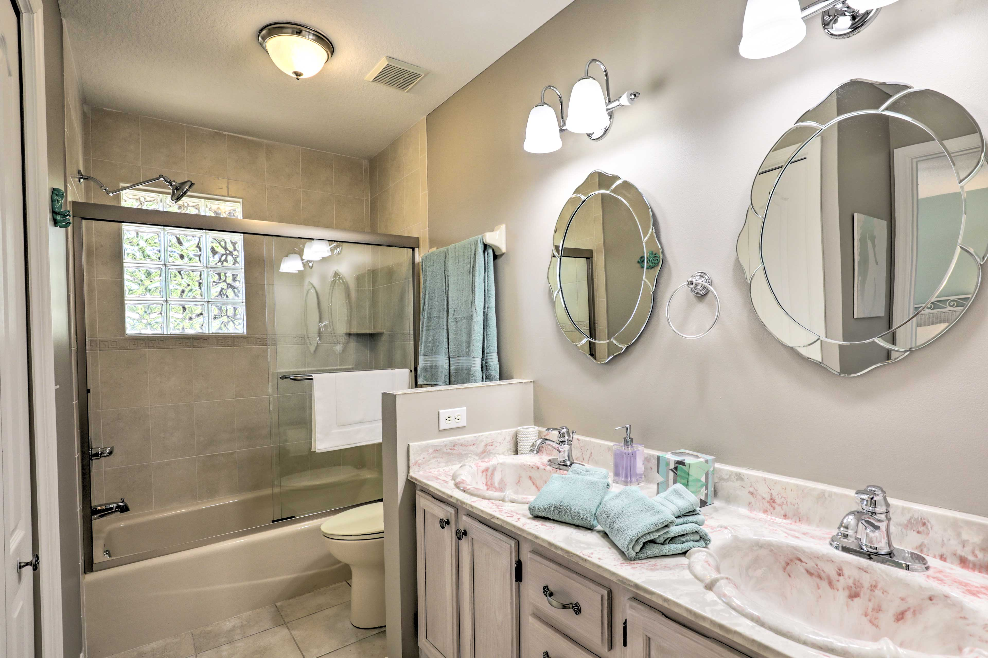 This bathroom features a double-sink vanity and shower/tun combo.