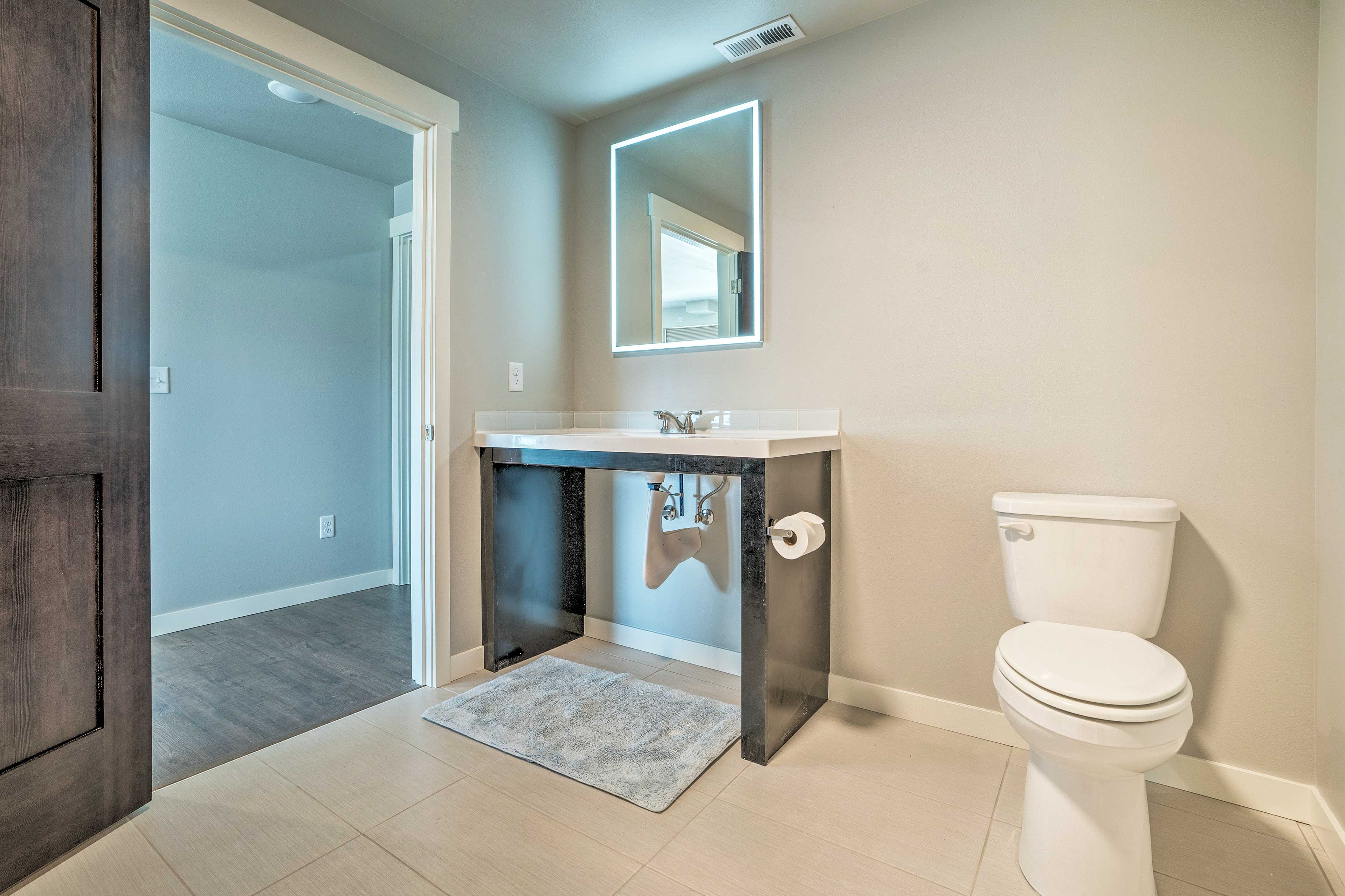 Store your toiletries on the vanity of this first bedroom.