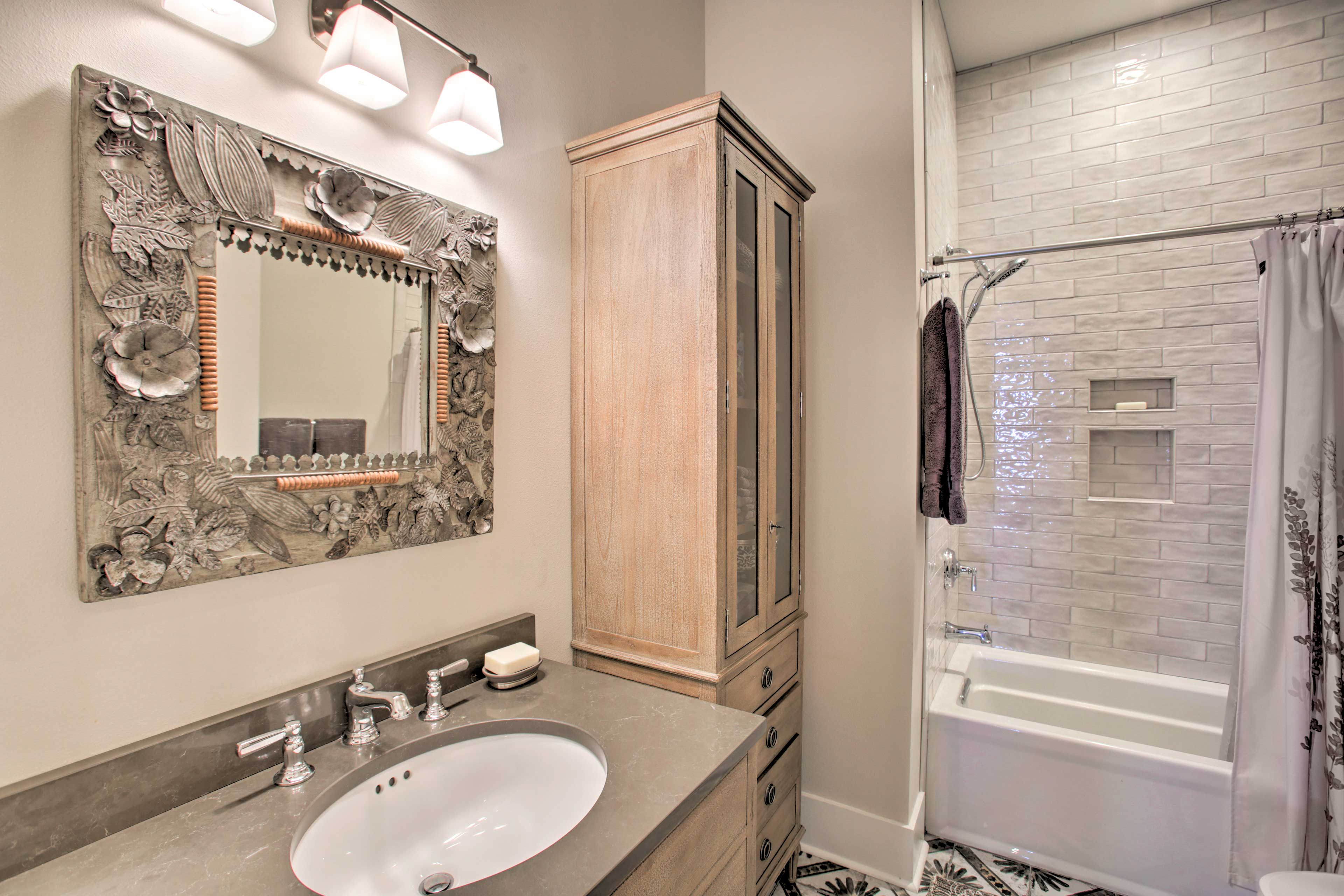 The second bathroom is outfitted with a shower/tub combo and sleek tiles.