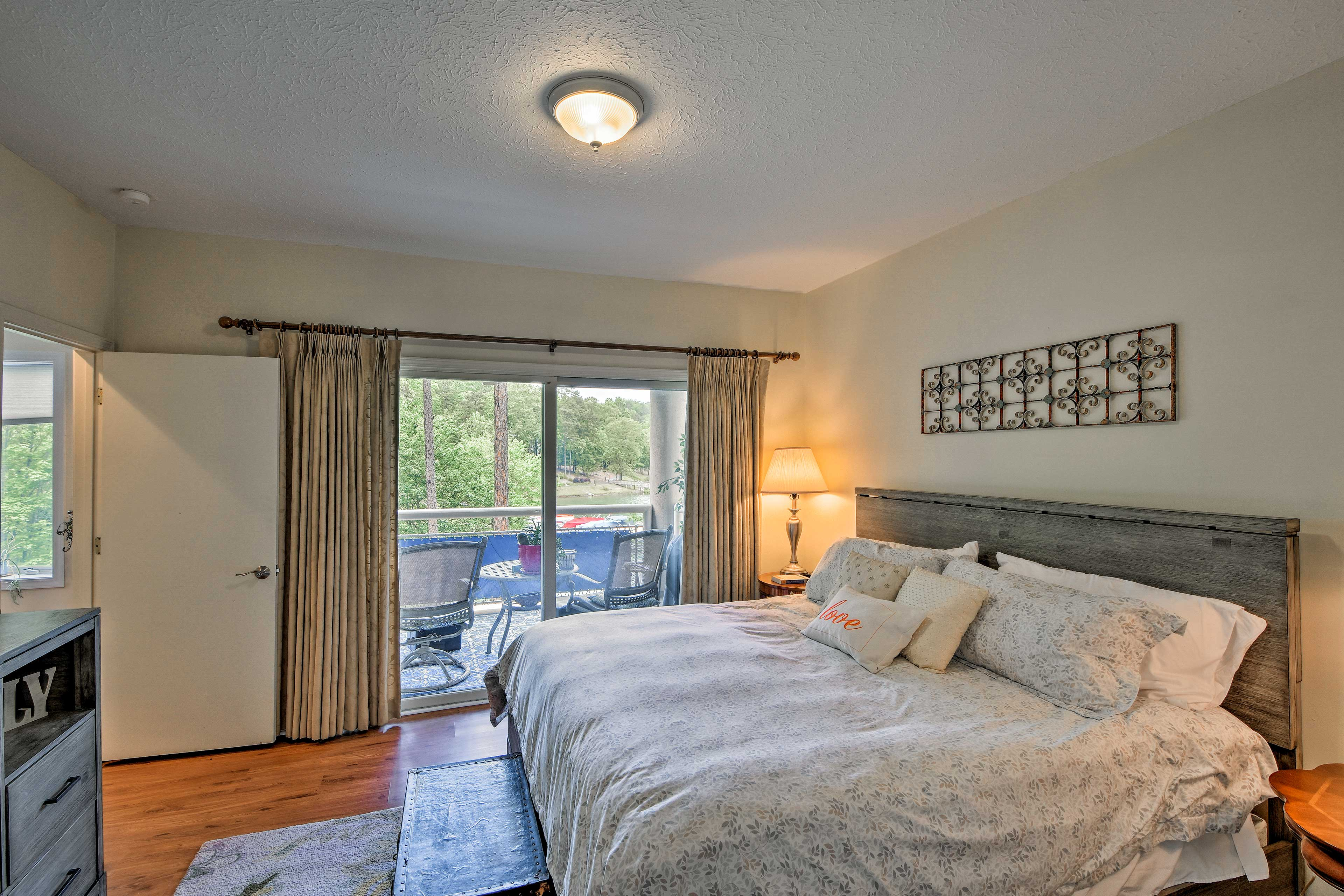 The bedroom boasts access to the furnished balcony.