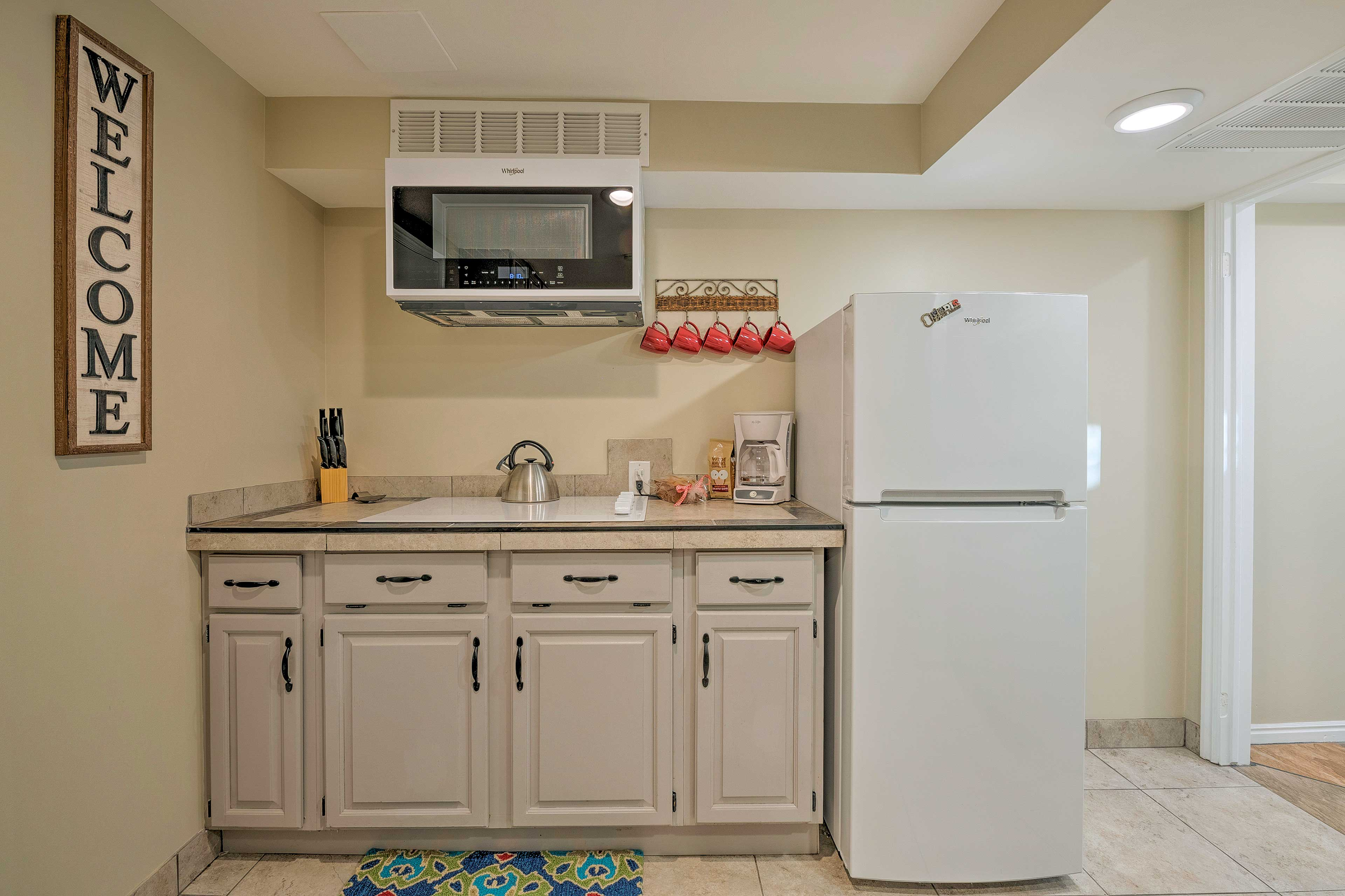 The kitchenette is well equipped with a stove top, fridge, and more.