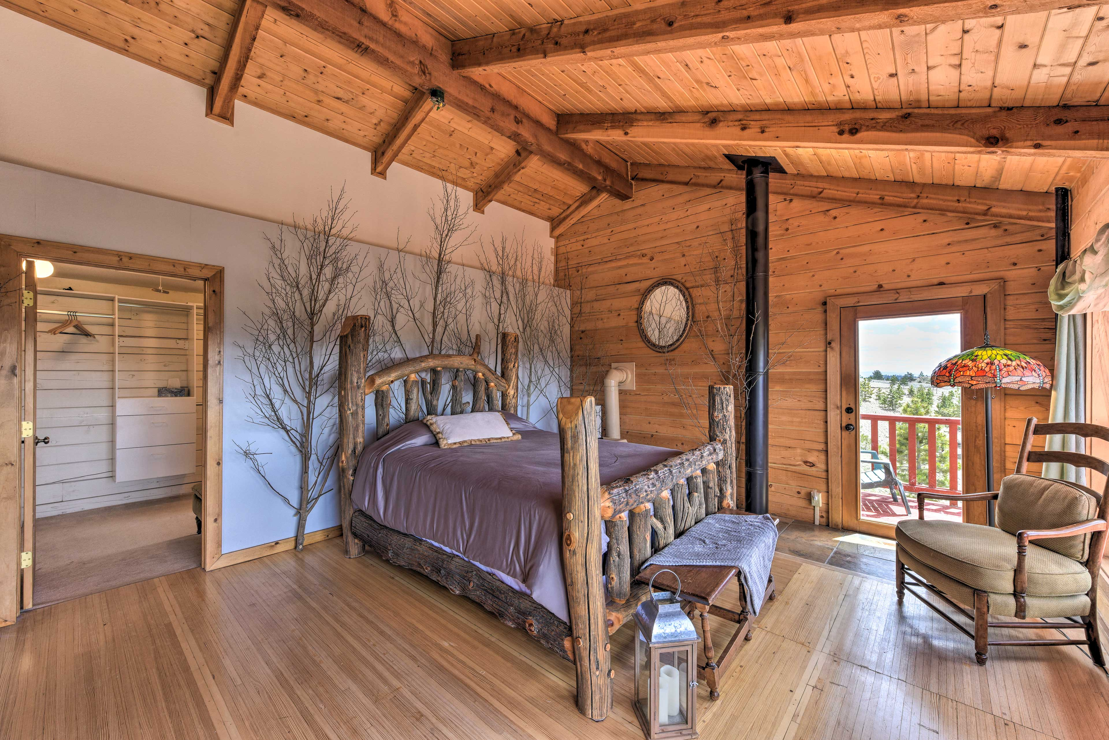 This spacious master bedroom features high ceilings and rustic decor.