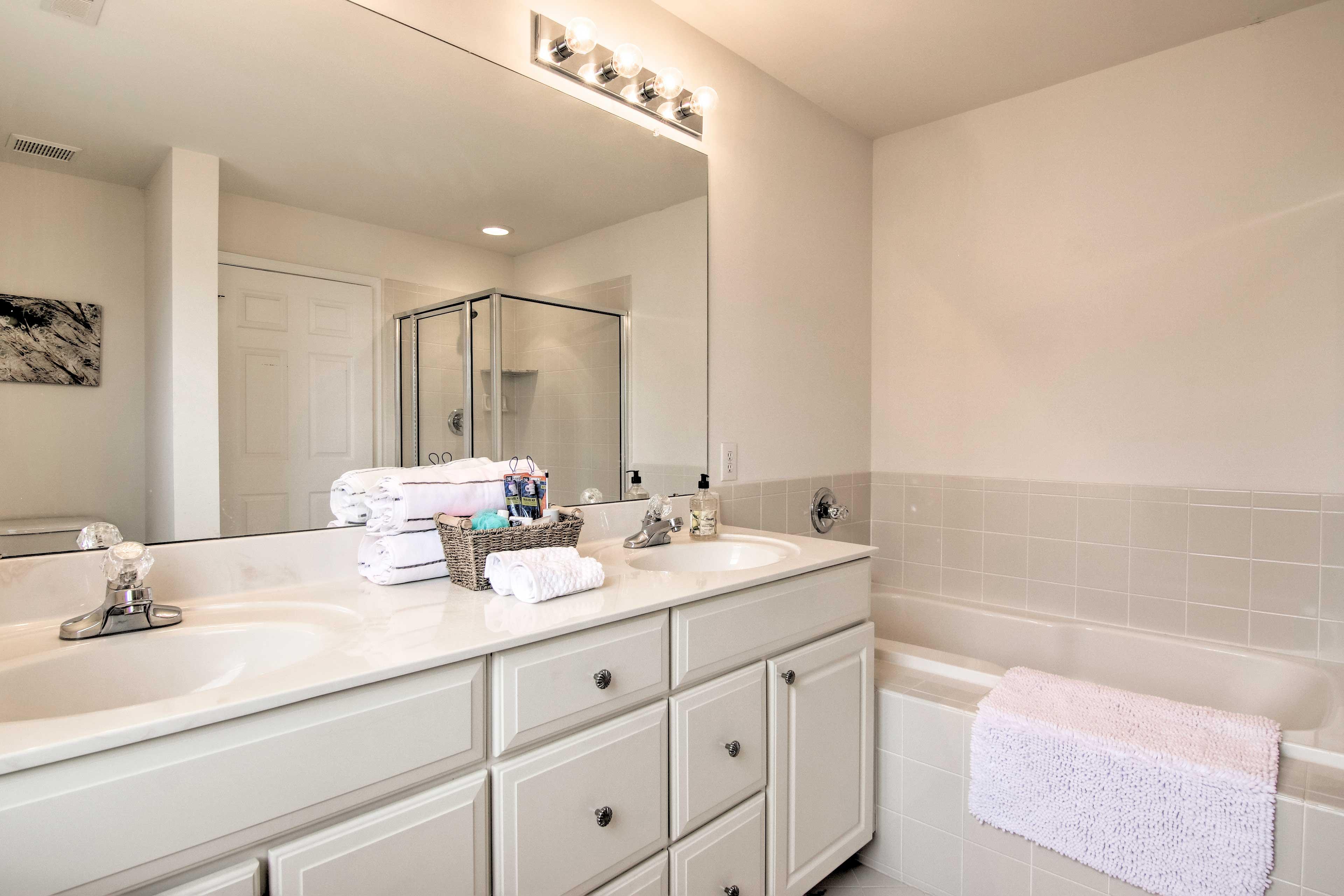 The en-suite bathroom features a soaking tub, dual sinks & walk-in shower.