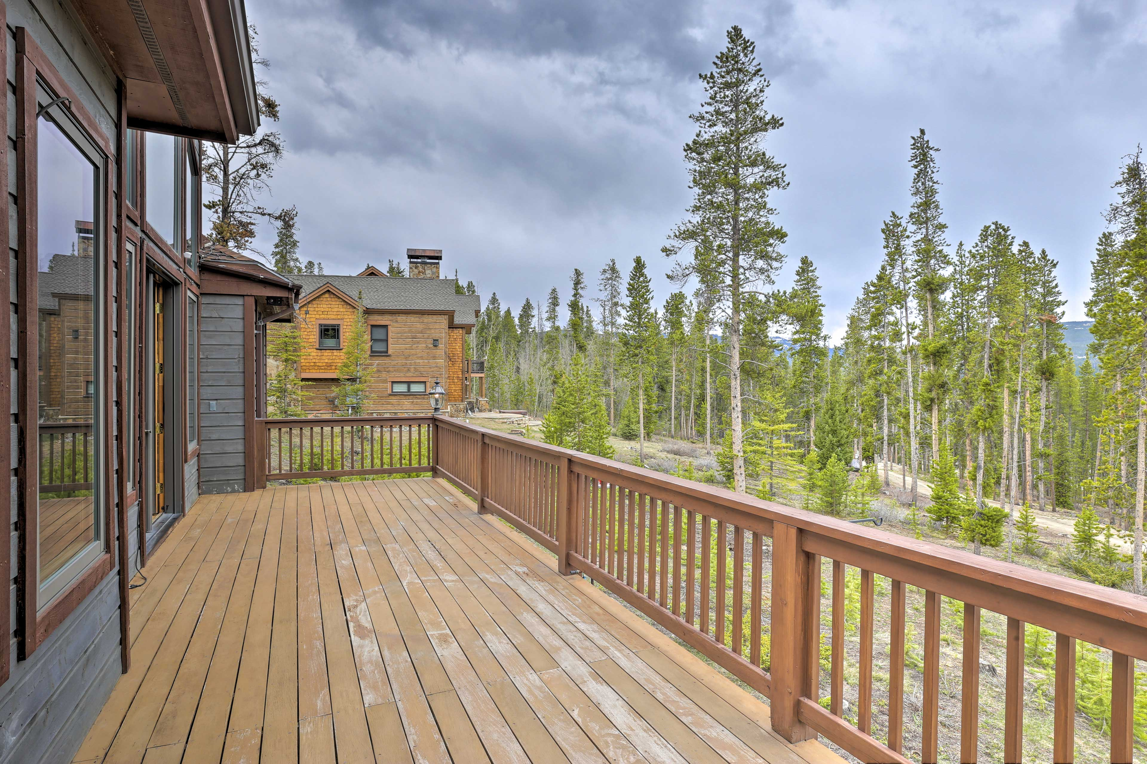 View from the house include towering trees & mountain silhouettes.