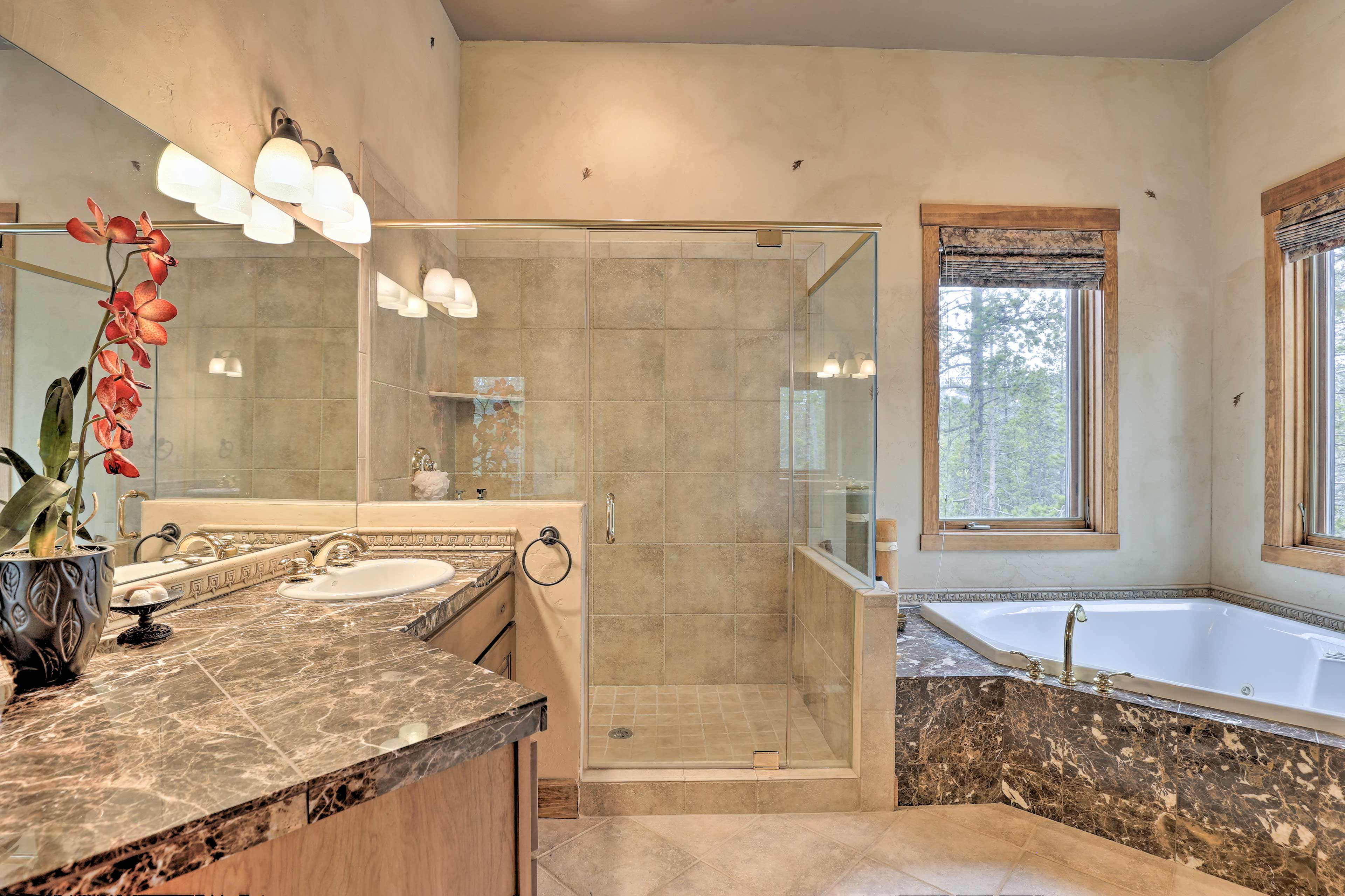 The master bath boasts a gorgeous granite-topped vanity, shower, & tub.