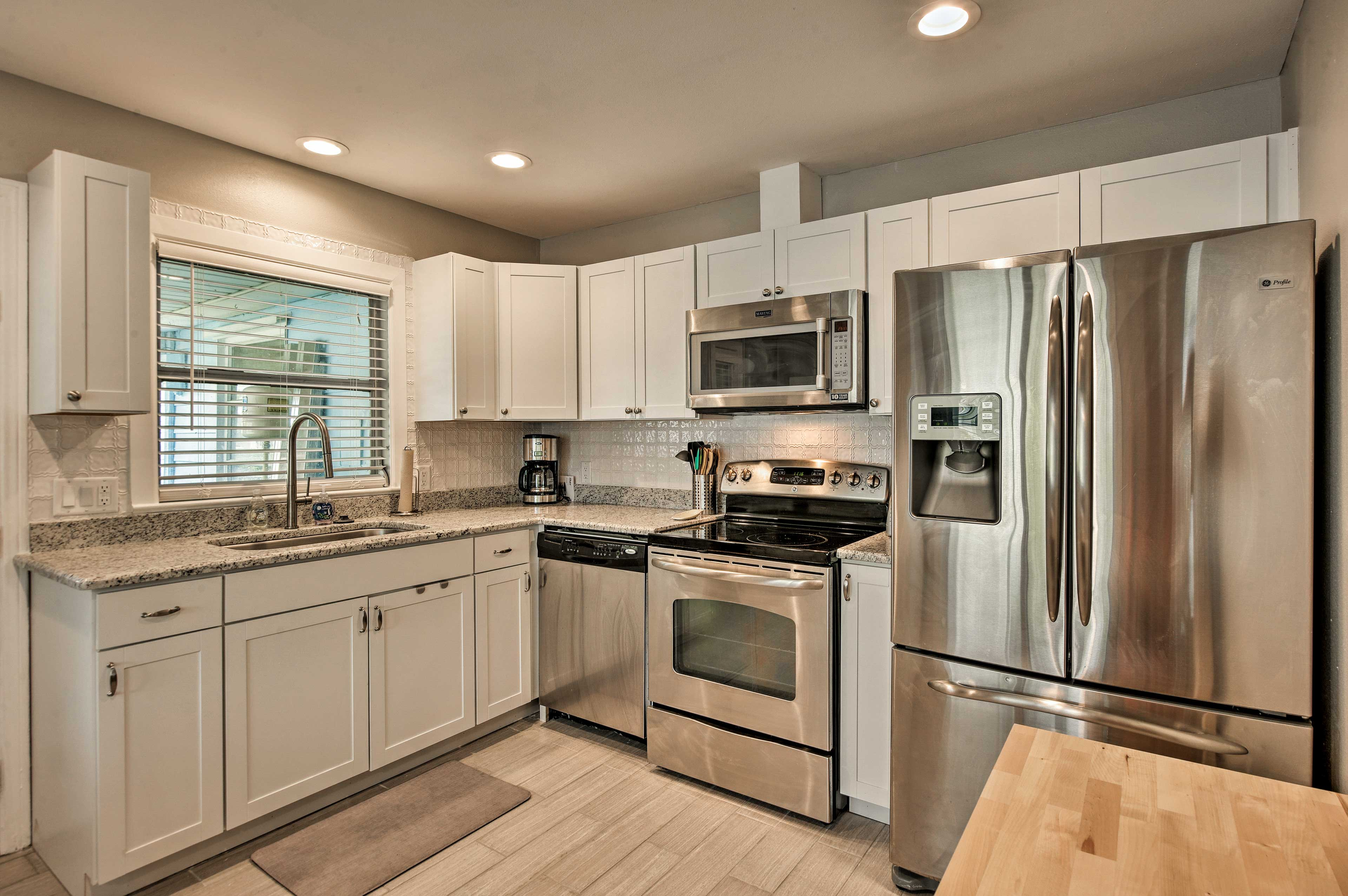 Crisp while cabinets and stainless steel appliances elevate the space.