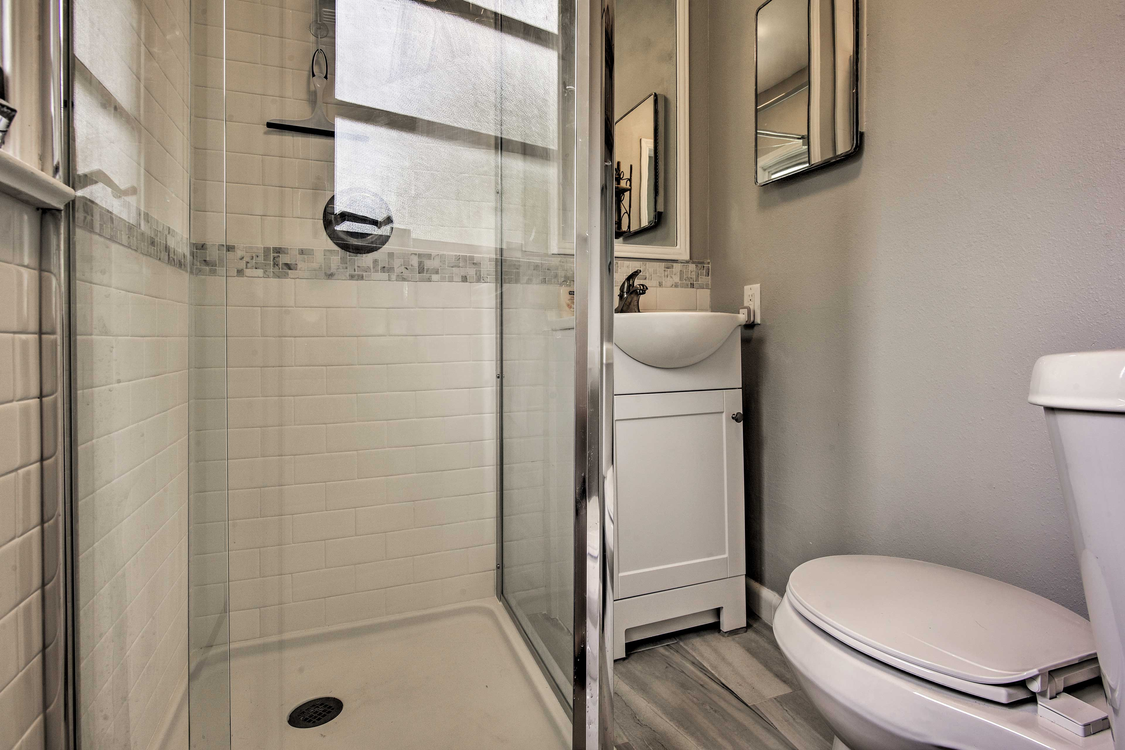The second bedroom boasts a glass-enclosed shower.