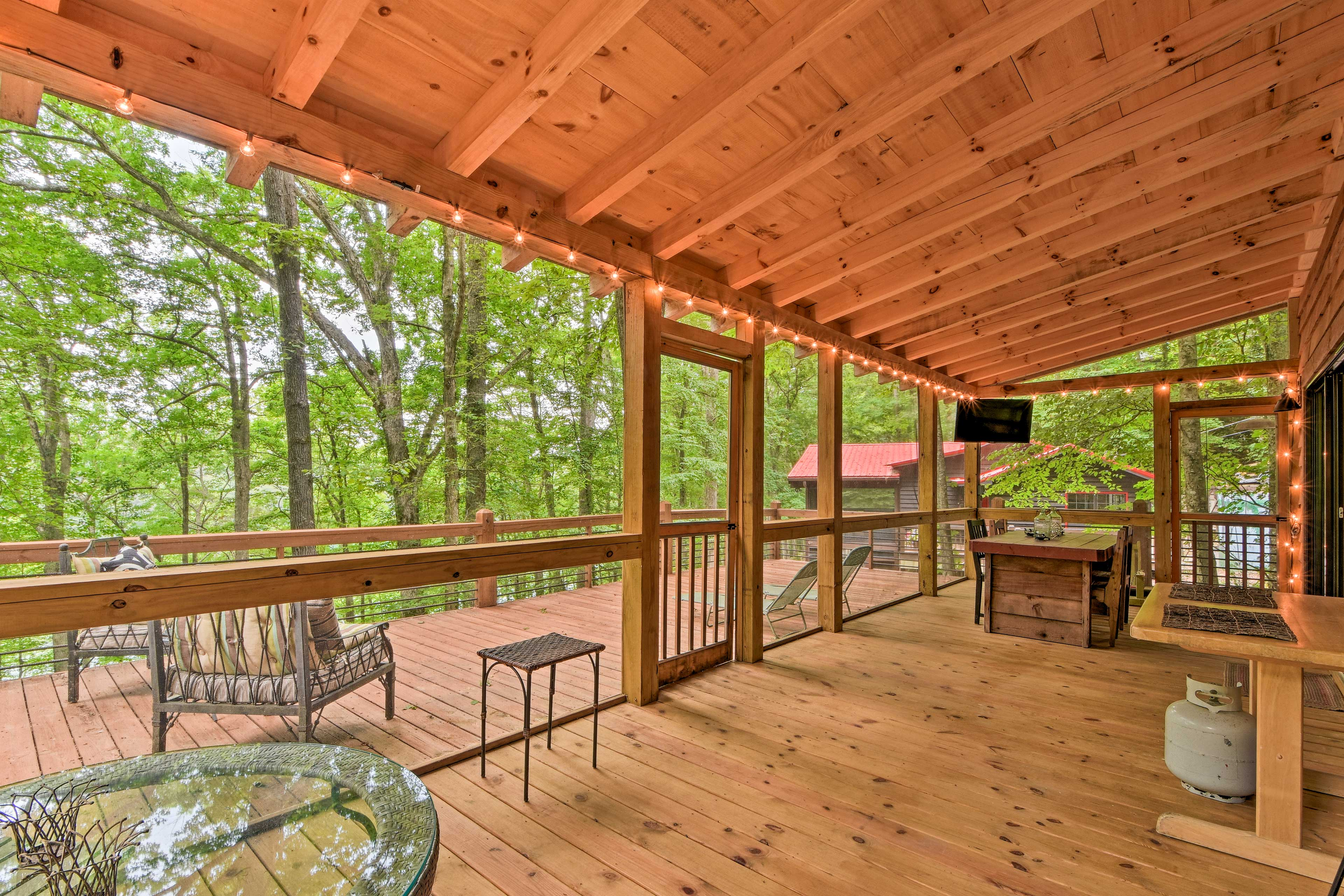 The screened porch boasts a flat-screen TV, hanging lights, and dining for 6.