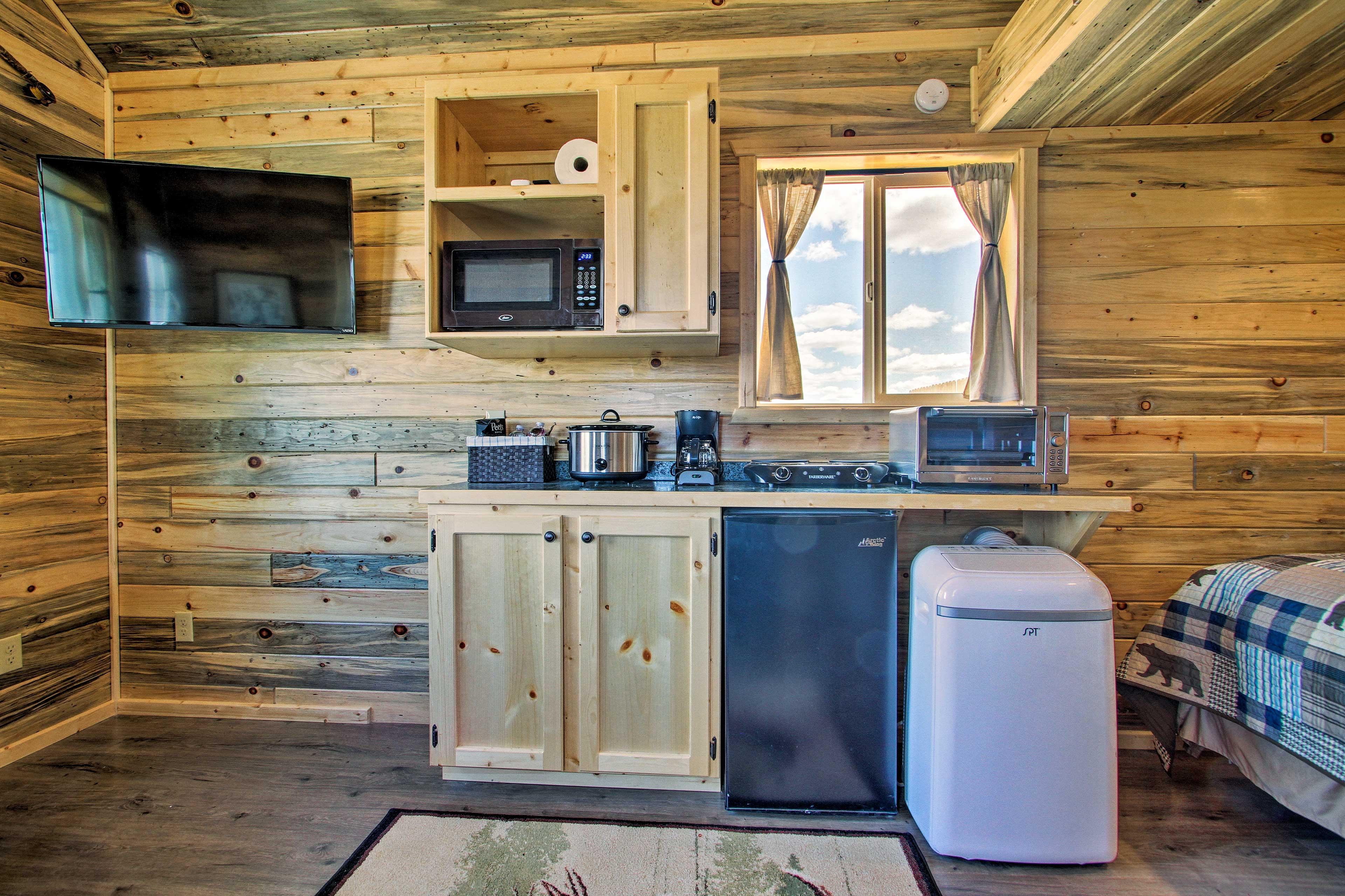 The kitchenette features appliances like a mini-fridge, crock pot & stove top.